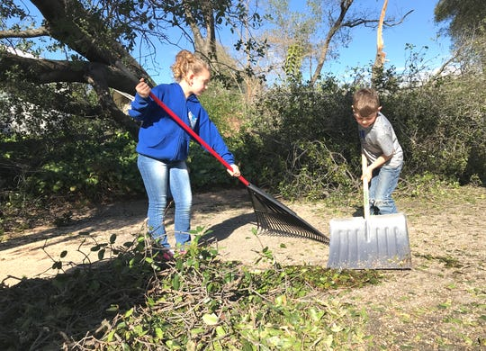Lily Howard, 8, left, and her brother Rylen Howard, 5, clean leaves and branches off Terrace Drive in front of their home Saturday where last week's snowstorm knocked trees into the roadway.