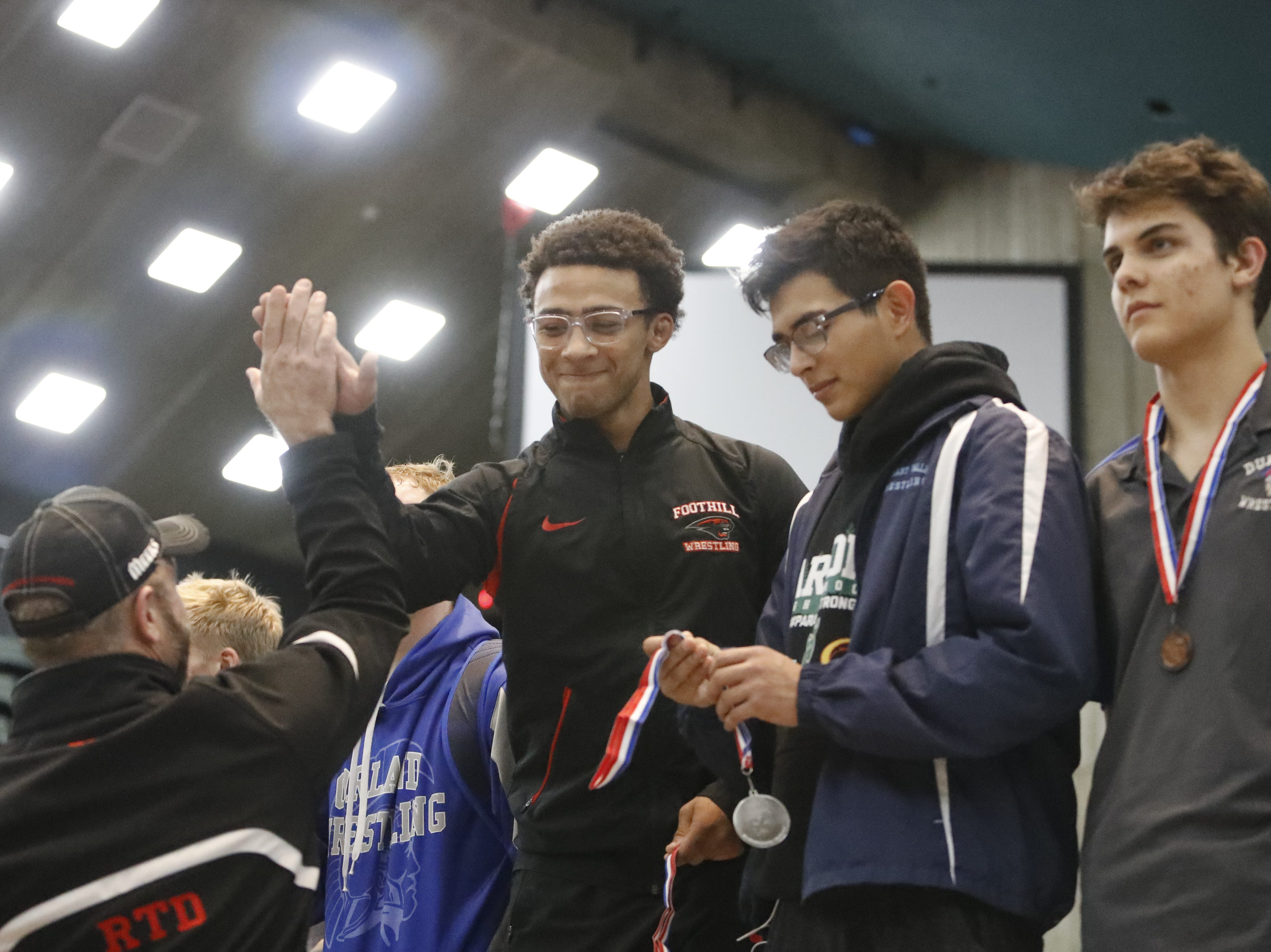 Foothill wrestler Earnest Wilson high-fives a coach from the podium after taking first place in the 145-pound weight class at Northern Section championships on Friday, Feb. 15, at the Redding Civic Auditorium.