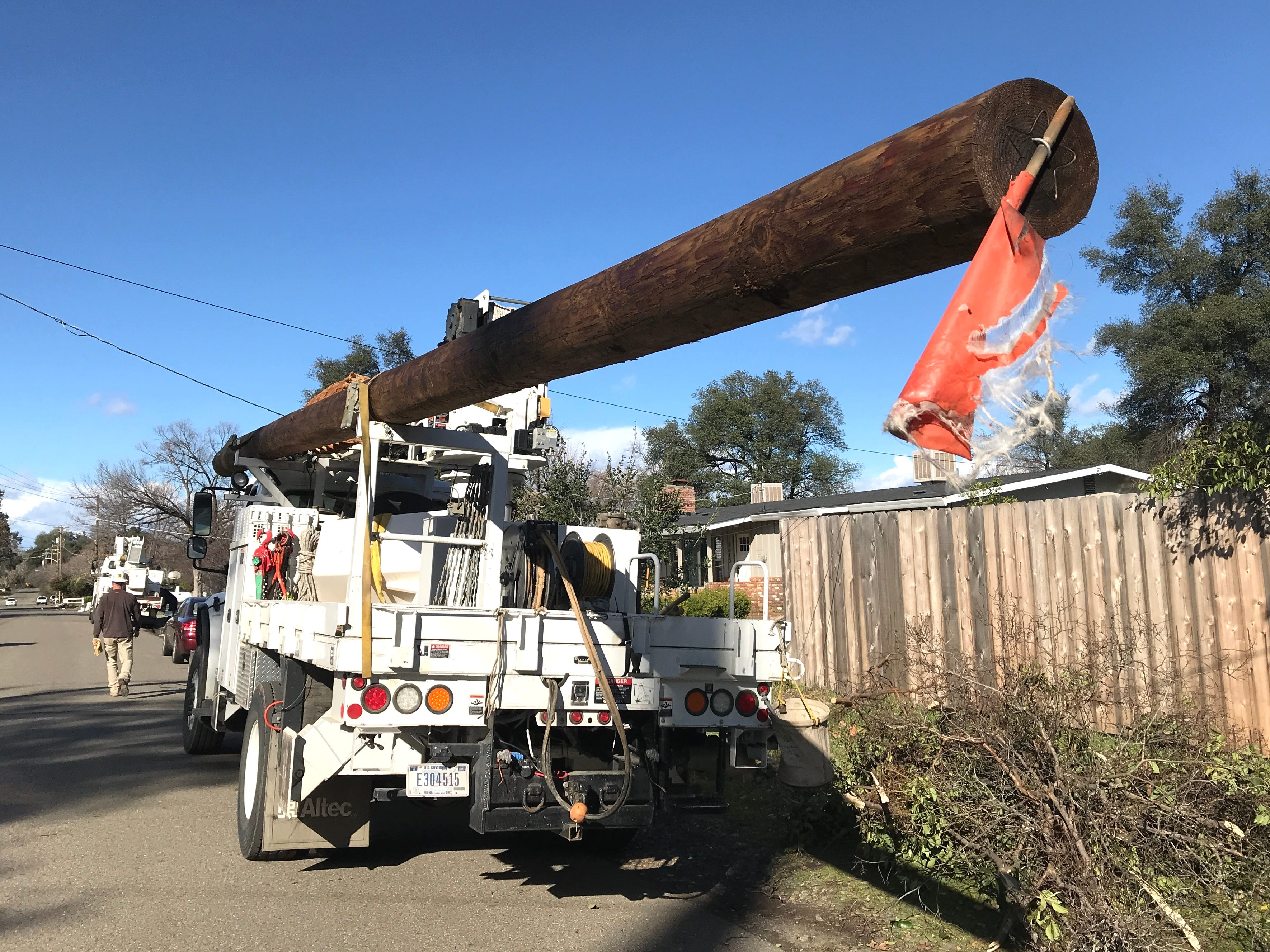 A truck hauls a power pole along Ricardo Avenue where utility crews were working Saturday to restore power in the south Redding neighborhood.