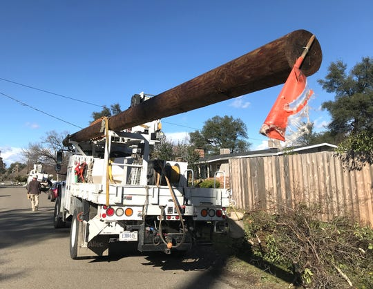 A truck hauls a power pole along Ricardo Avenue where utility crews were working Saturday, Feb. 16, 2019 to restore power in the south Redding neighborhood.
