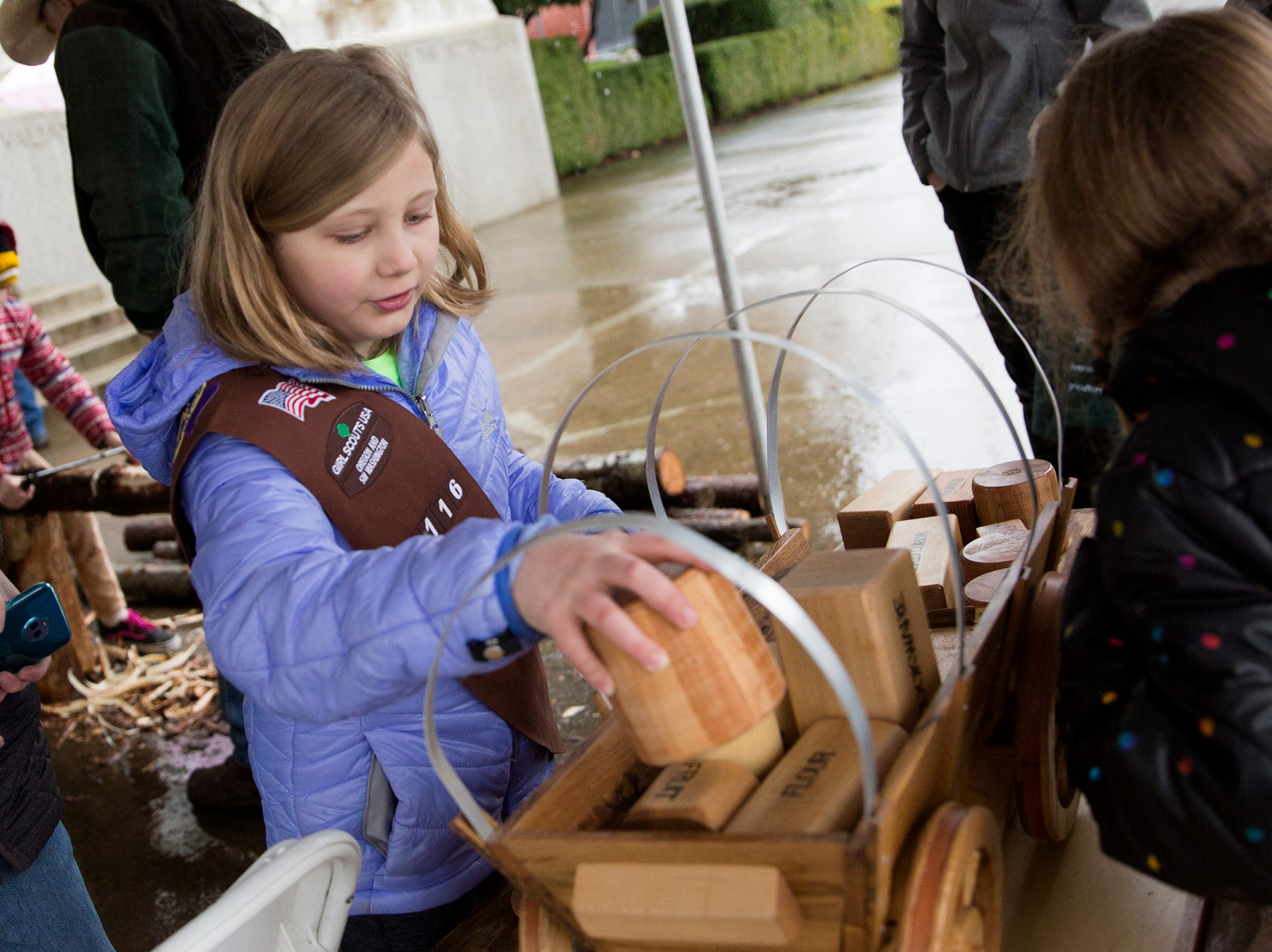 Girl Scout Brinleigh Grinberg stacks blocks representing food items and personal belongings in a toy wagon provided by the Yamhill Valley Heritage Center during Oregon's 160th Birthday Celebration at the Oregon State Capitol in Salem on Saturday, Feb. 16, 2019.