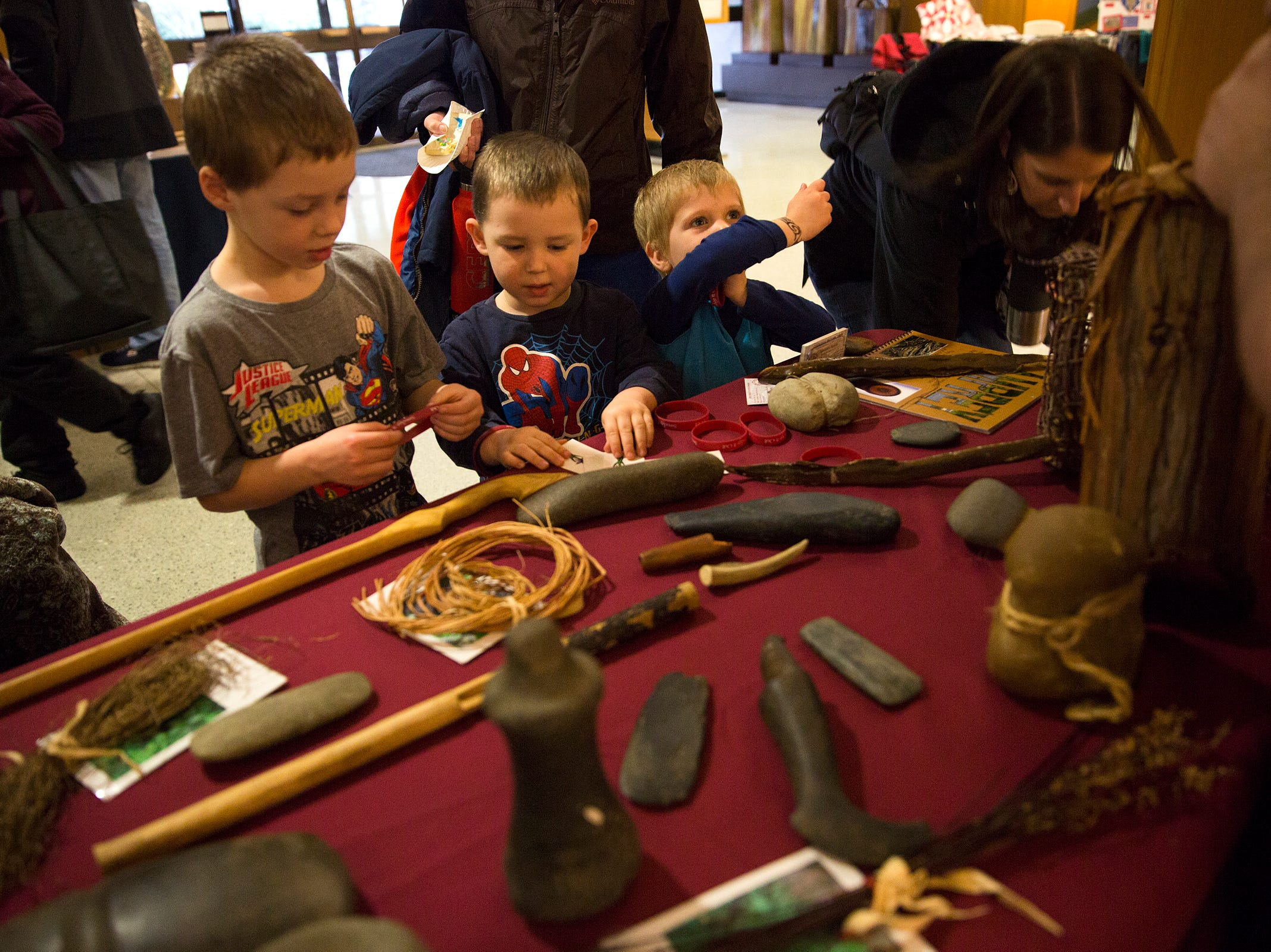Knox Howard, Ford Howard and Theo Erich play with hunting and gathering tools used by the Coquille Indian Tribe during Oregon's 160th Birthday Celebration at the Oregon State Capitol in Salem on Saturday, Feb. 16, 2019.