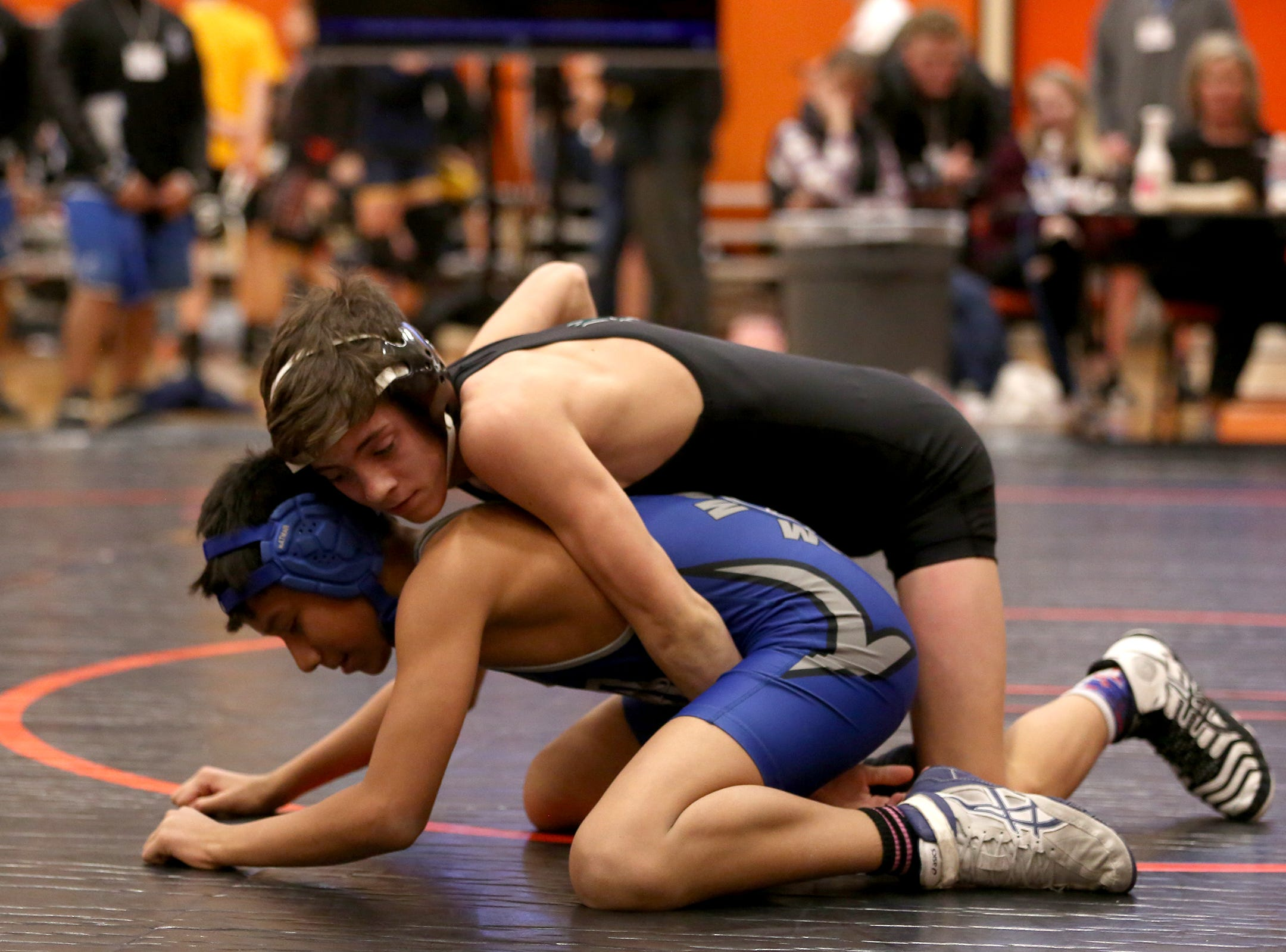 West Salem's Brett McClung holds down McNary's Damien Hernandez in the 106 pound weight class during the Mountain Valley Conference district wrestling tournament at Sprague High School in Salem on Friday, Feb. 15, 2019.