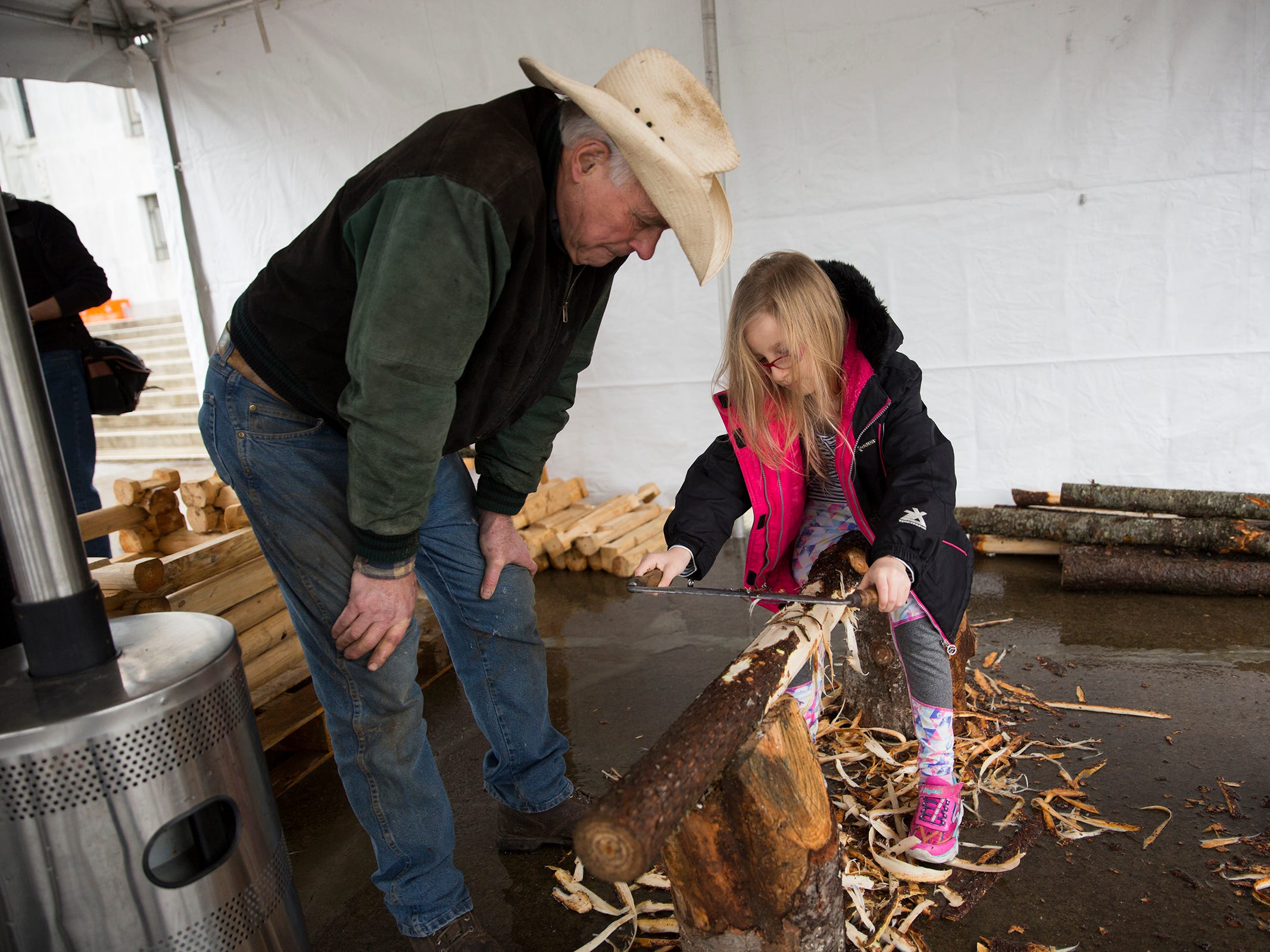 Gonn Callaham helps Eva Wolff, 7, learn to carve wood during Oregon's 160th Birthday Celebration at the Oregon State Capitol in Salem on Saturday, Feb. 16, 2019.