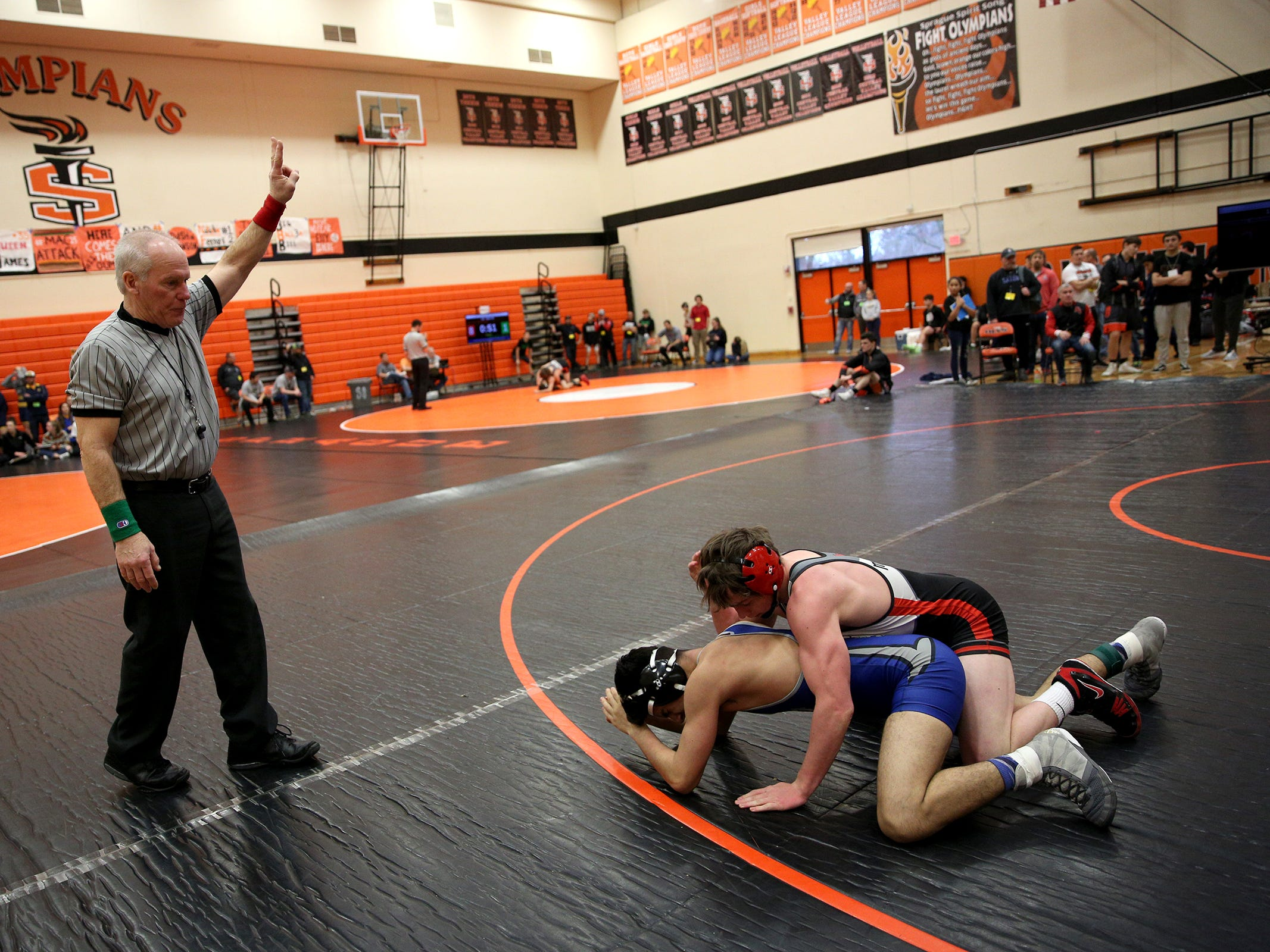 Mountain View's Beau Olson holds down McNary's Giovanni Cervantes as they compete in the 138 pound weight class during the Mountain Valley Conference district wrestling tournament at Sprague High School in Salem on Friday, Feb. 15, 2019.