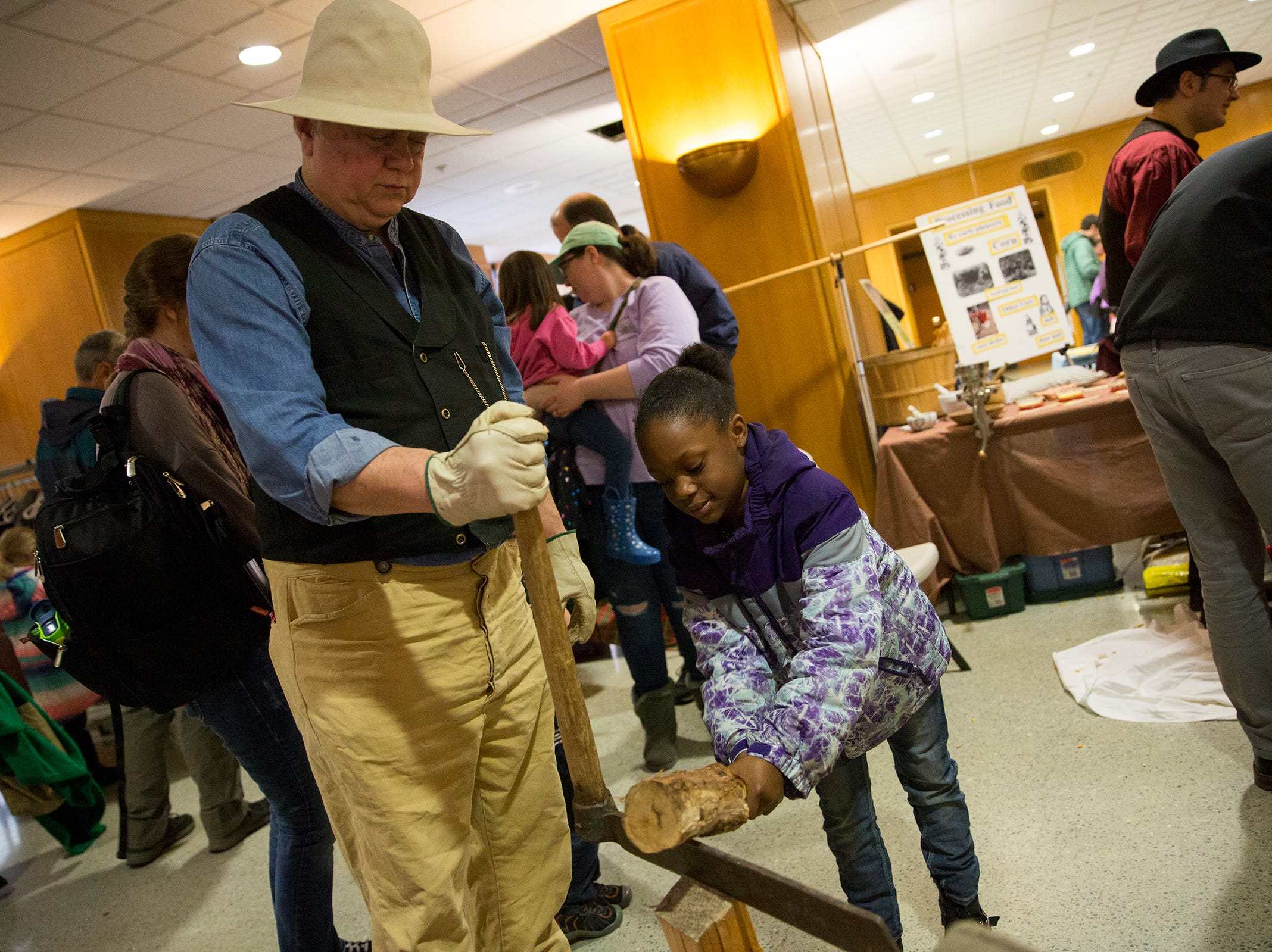 Joe Baron helps Z'amara Ratler, 9, learn how to chop wood during Oregon's 160th Birthday Celebration at the Oregon State Capitol in Salem on Saturday, Feb. 16, 2019.