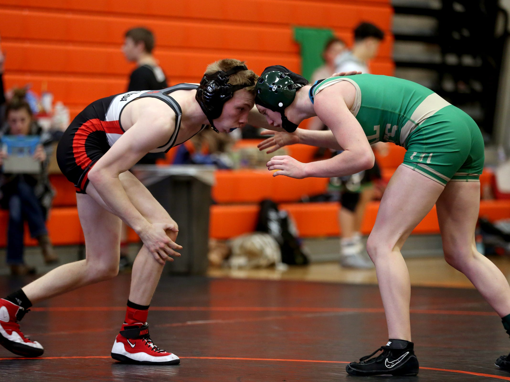 Mountain View's Tyson Oliver (left) and McKay's Tess Barnett compete in the 113 pound weight class during the Mountain Valley Conference district wrestling tournament at Sprague High School in Salem on Friday, Feb. 15, 2019.