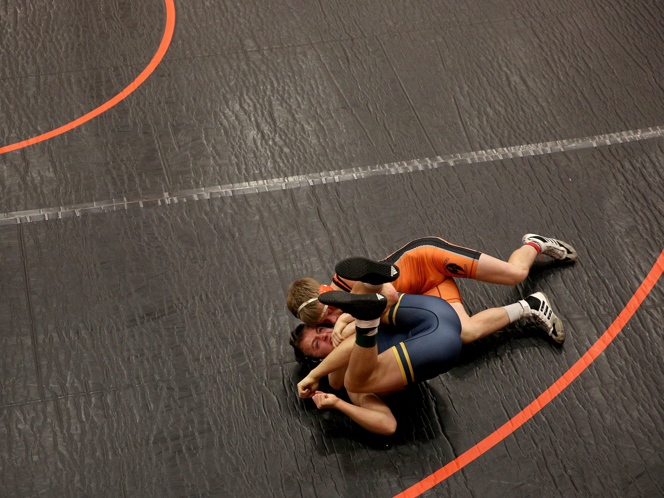 Sprague's Luke Merzenich holds down Bend's Kellen Murphy as they compete in the 138 pound weight class during the Mountain Valley Conference district wrestling tournament at Sprague High School in Salem on Friday, Feb. 15, 2019.