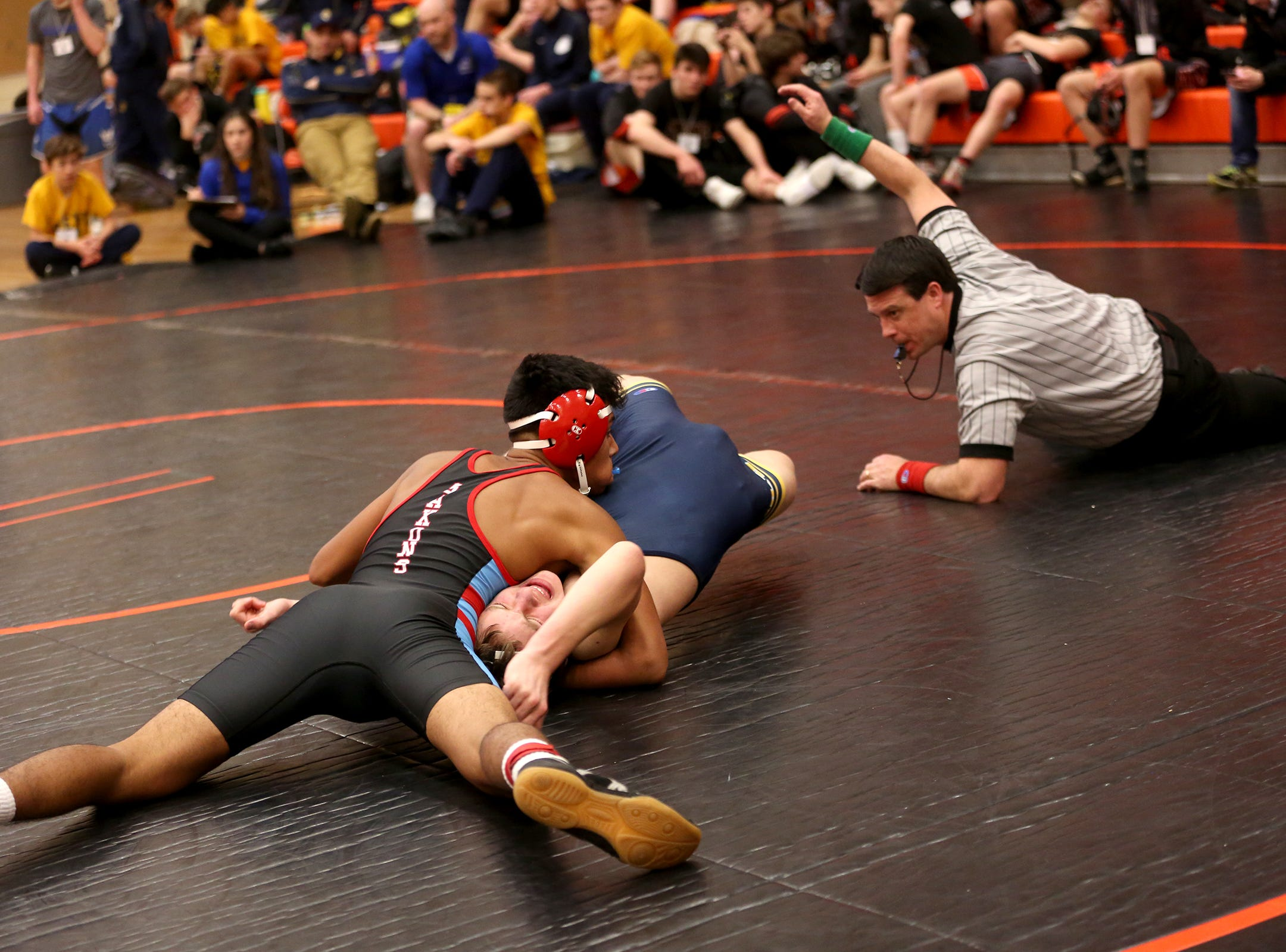 South Salem's Marco Garcia holds down Bend's Charles Powell as they compete in the 145 pound weight class during the Mountain Valley Conference district wrestling tournament at Sprague High School in Salem on Friday, Feb. 15, 2019.