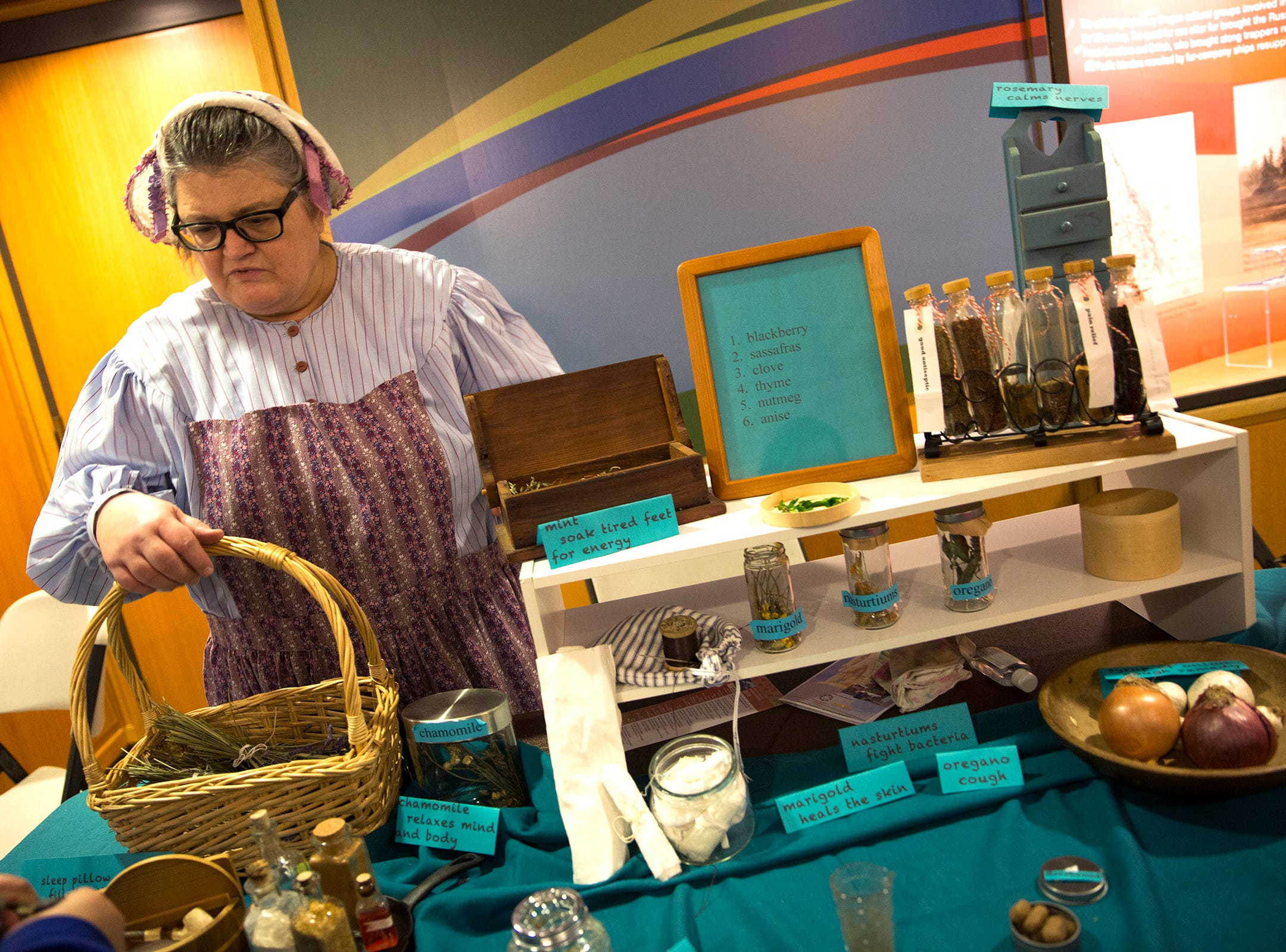 Janet Land, dressed as a granny doctor from the 1850's, shows some of the items used in that era during Oregon's 160th Birthday Celebration at the Oregon State Capitol in Salem on Saturday, Feb. 16, 2019.