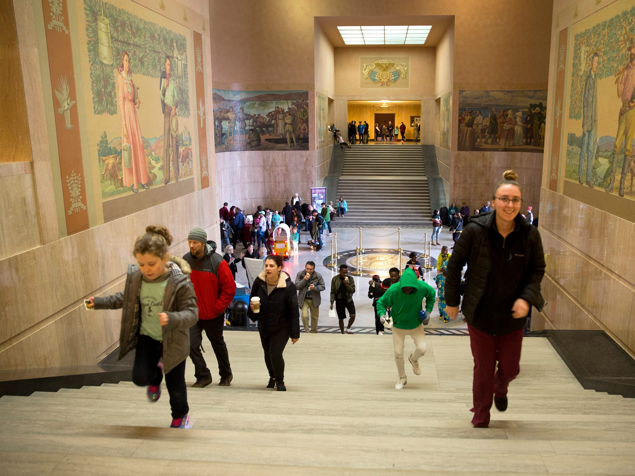 People rush up the steps to the Senate Chambers during Oregon's 160th Birthday Celebration at the Oregon State Capitol in Salem on Saturday, Feb. 16, 2019.