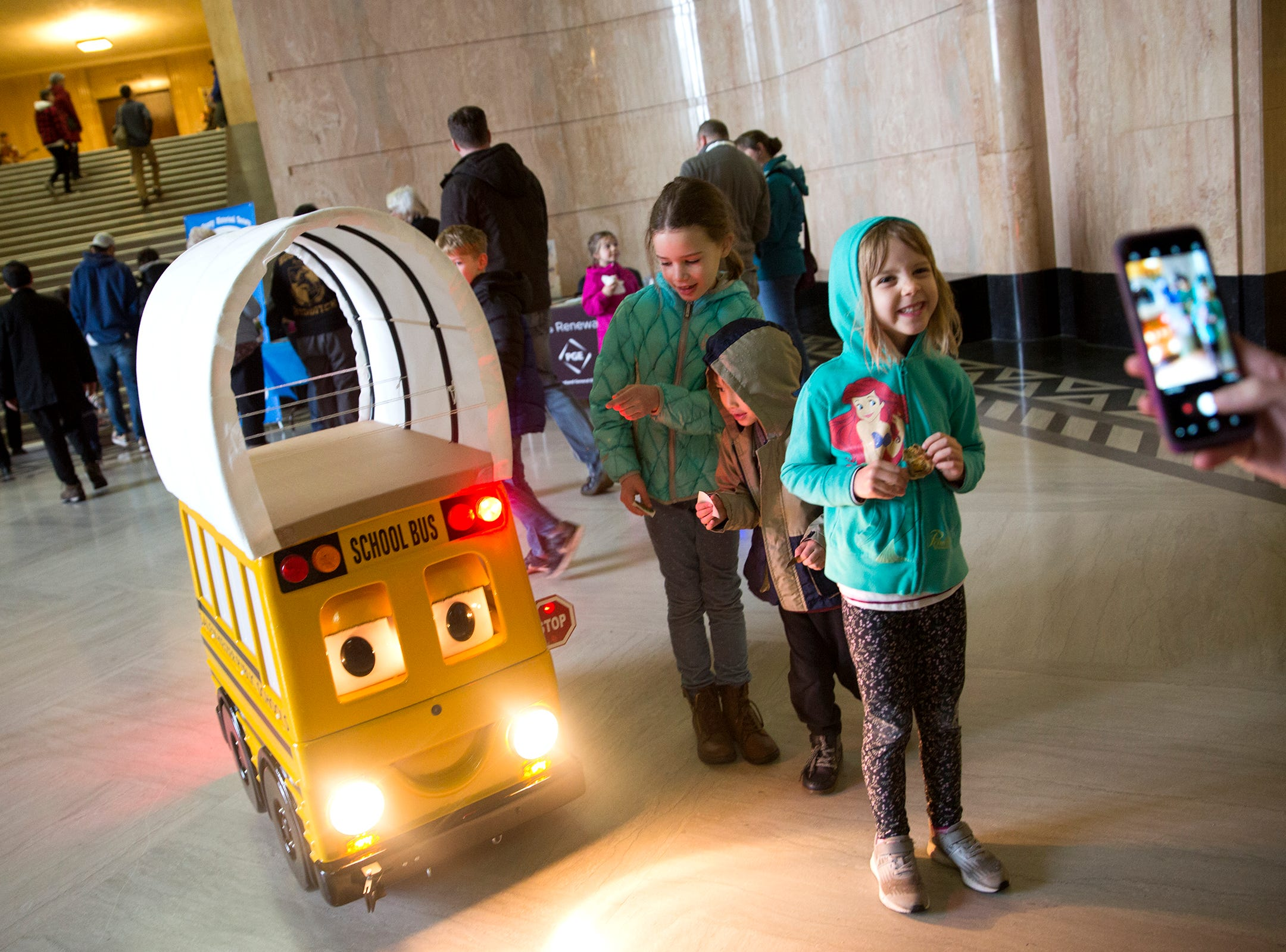 Grace Smucker, 7, Abby Smucker 5, and Nathan Smucker,4, of Independence pose for a photo with a Salem-Keizer school bus, dressed as a covered wagon, during Oregon's 160th Birthday Celebration at the Oregon State Capitol in Salem on Saturday, Feb. 16, 2019.