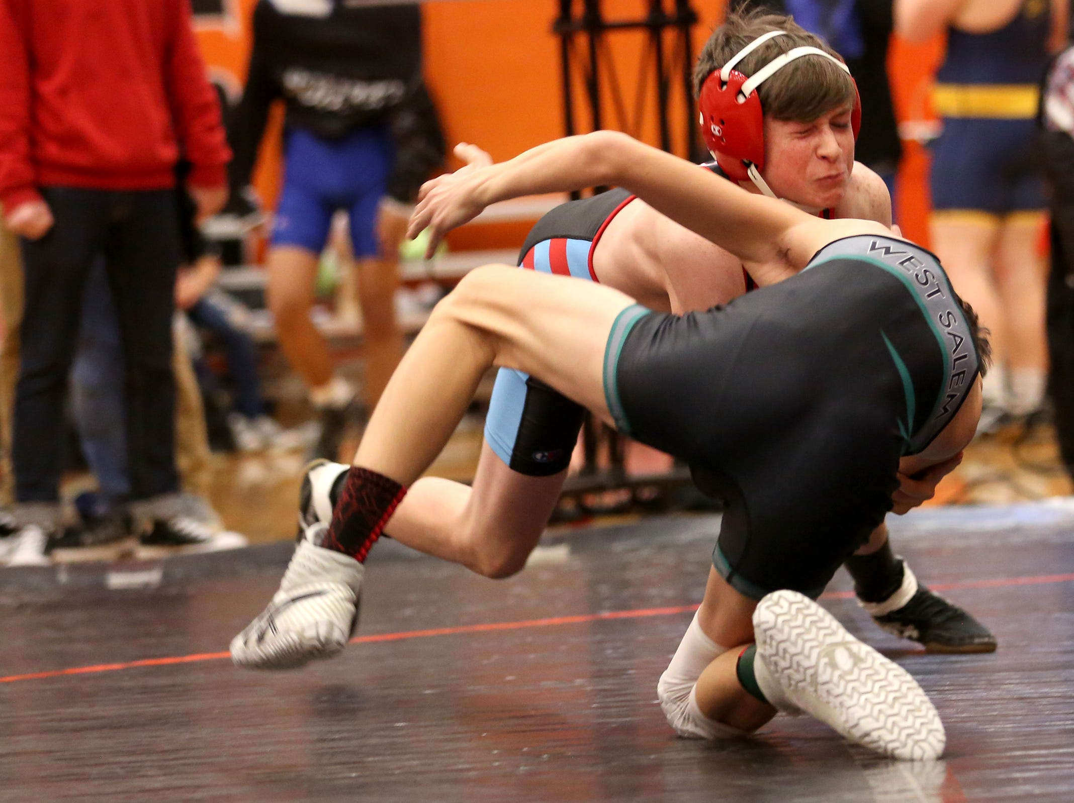 South Salem's Ethan Kline (facing) struggles against West Salem's Lance McClung in the 113 pound weight class during the Mountain Valley Conference district wrestling tournament at Sprague High School in Salem on Friday, Feb. 15, 2019.