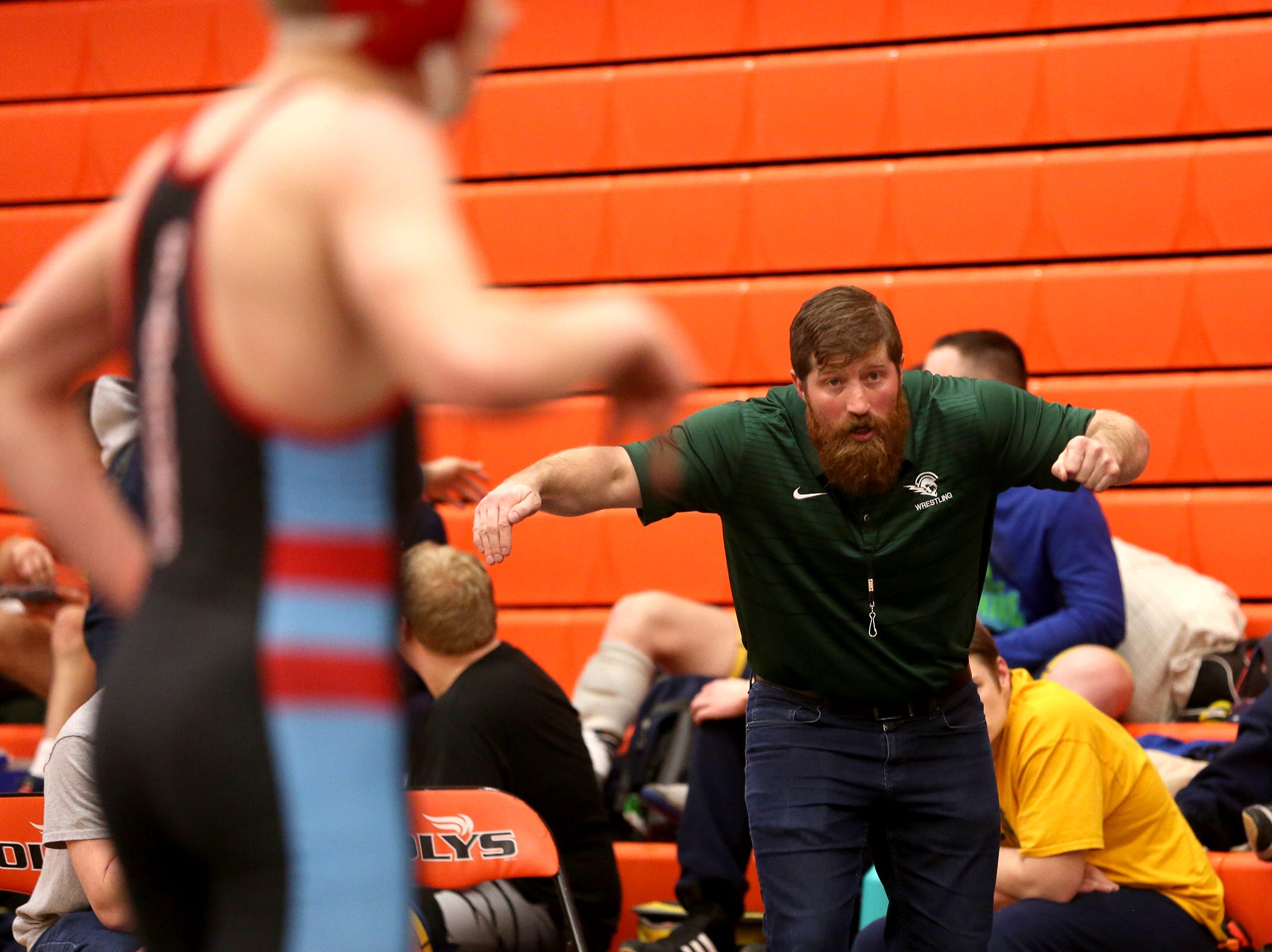 Assistant Wrestling Coach Tray Thomas demonstrates a move to one of his wrestlers during the Mountain Valley Conference district wrestling tournament at Sprague High School in Salem on Friday, Feb. 15, 2019.