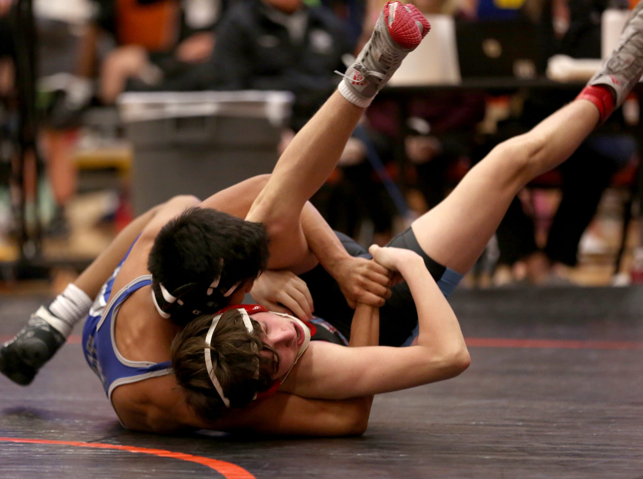 McNary's Daniel Hernandez holds on to South Salem's Hunter Harrison as they compete in the 126 pound weight class during the Mountain Valley Conference district wrestling tournament at Sprague High School in Salem on Friday, Feb. 15, 2019.