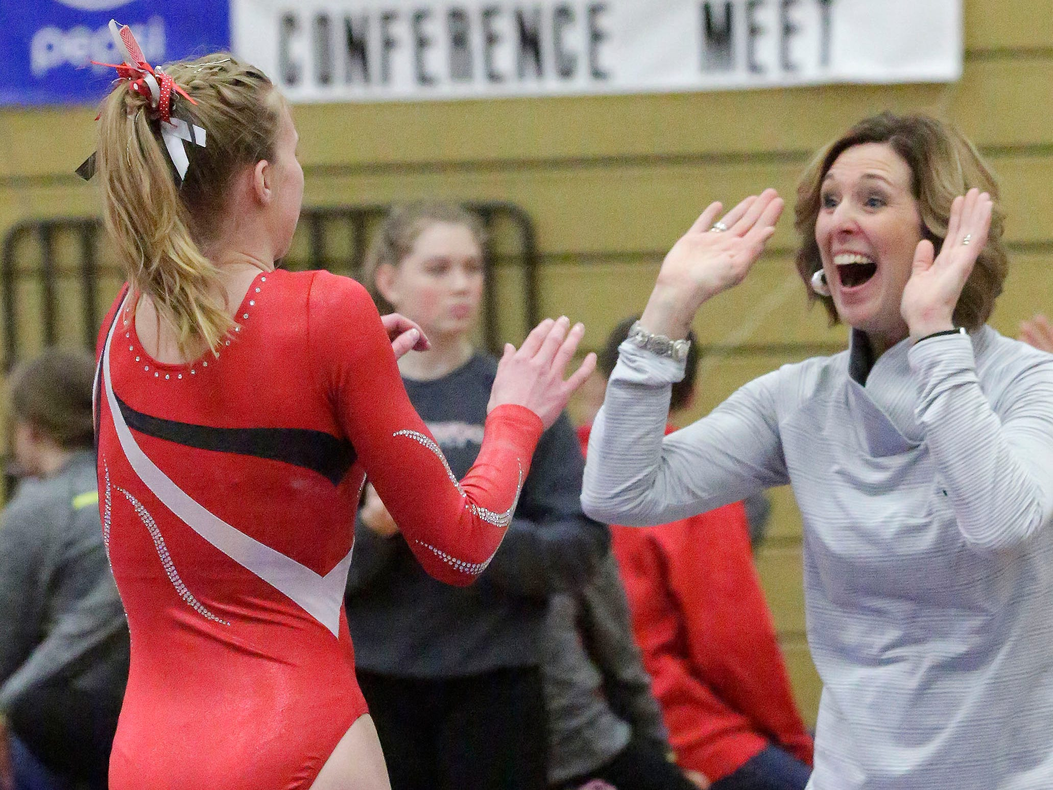 Manitowoc Lincoln coach Jacque Bartow is all smiles following a balance beam routine by an unidentified gymnasts during the WIAA Eastern Valley Conference Gymnastics Meet at Sheboygan South, Friday, February 15, 2019, in Sheboygan, Wis.