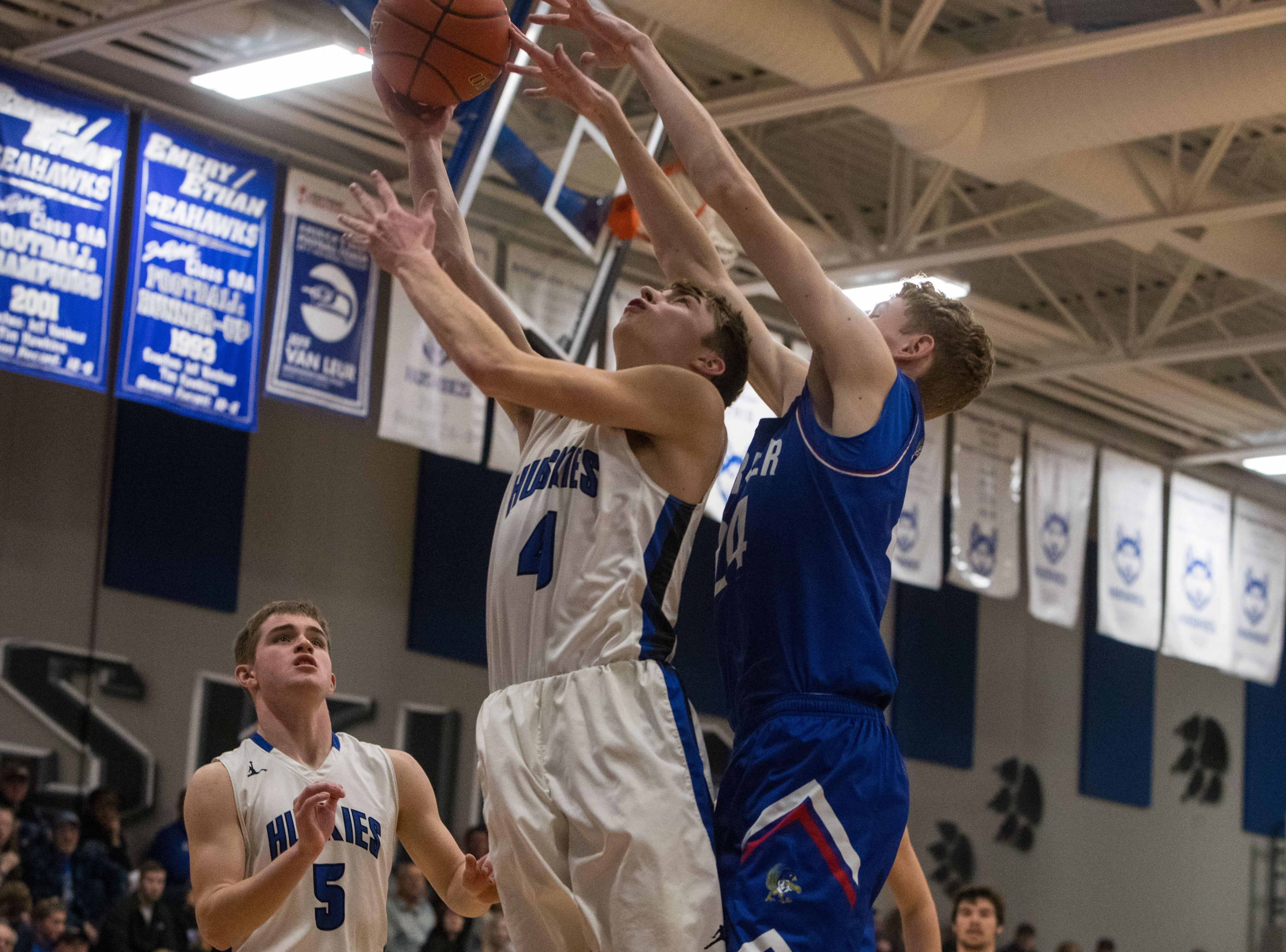 Parker's Camden Bialas (24) tries to block Bridgewater Emery's Chase Arend (4) from making a shot during a game in Emery, S.D., Feb. 15, 2019.