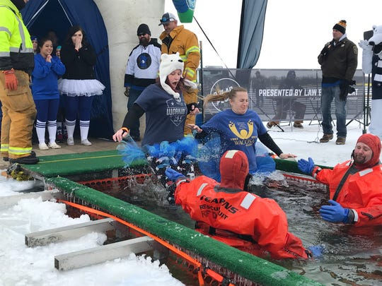 Stephanie Nelson, from Sauk Rapids, and Lisa Eggersgluess, from Sartell, jump during the Polar Plunge Saturday, Feb. 16, at The 400 Club.