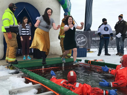 Kari Amundson (left), of St. Paul, and Abbie Wurster, of Alexandria, jump Saturday, Feb. 16, during the Polar Plunge at The 400 Club.