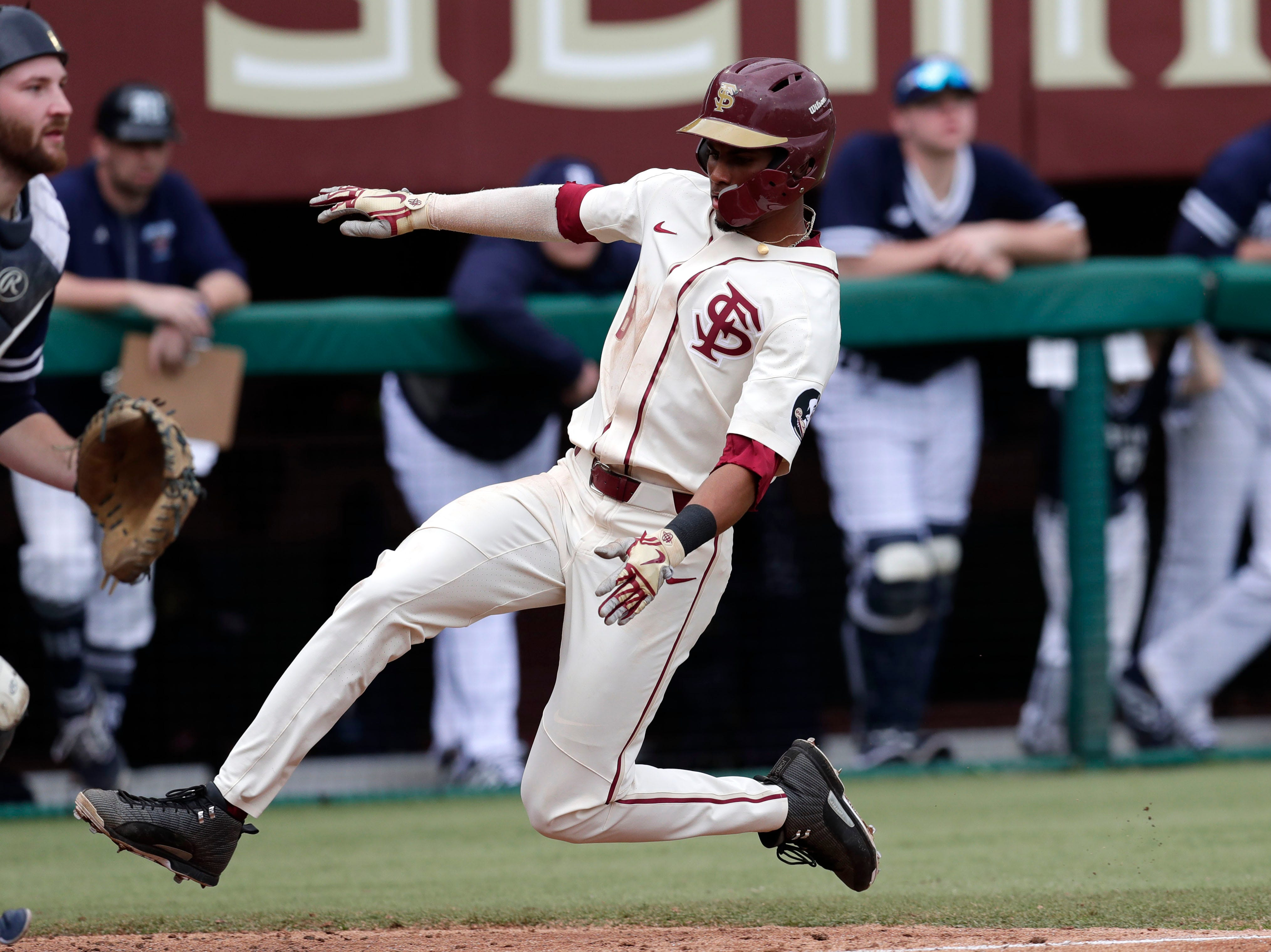 Florida State Seminoles outfielder/right handed Pitcher J.C. Flowers (8) slides into home plate to score another run for the Seminoles. The Florida State Seminoles host the Maine Black Bears for the second game of the series, Saturday Feb. 16, 2019.
