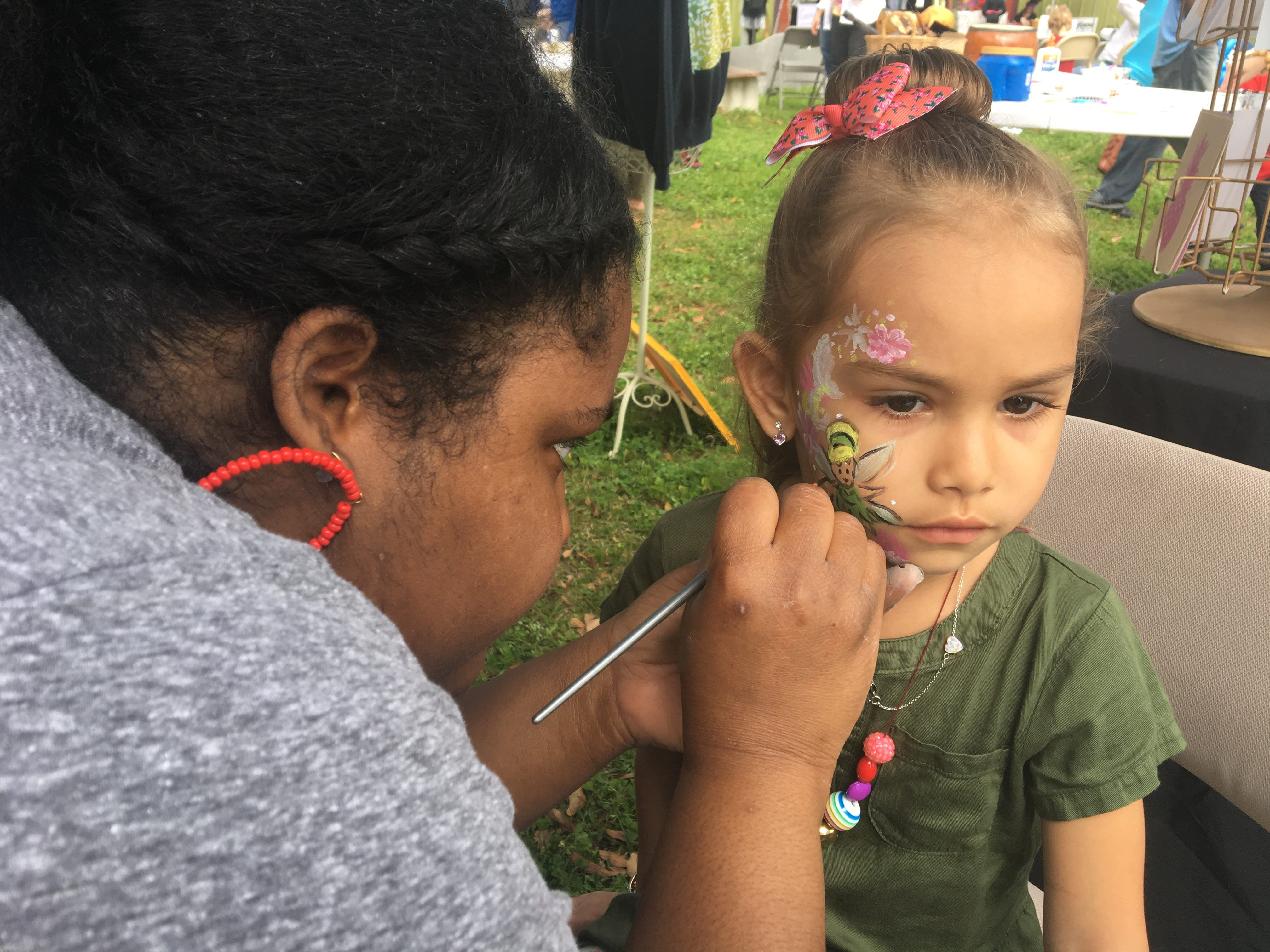 Penelope Villalona, 4, gets her face painted by The Fuzzy Pineapple's Nefetari Dannard at ArtiGras 2019.