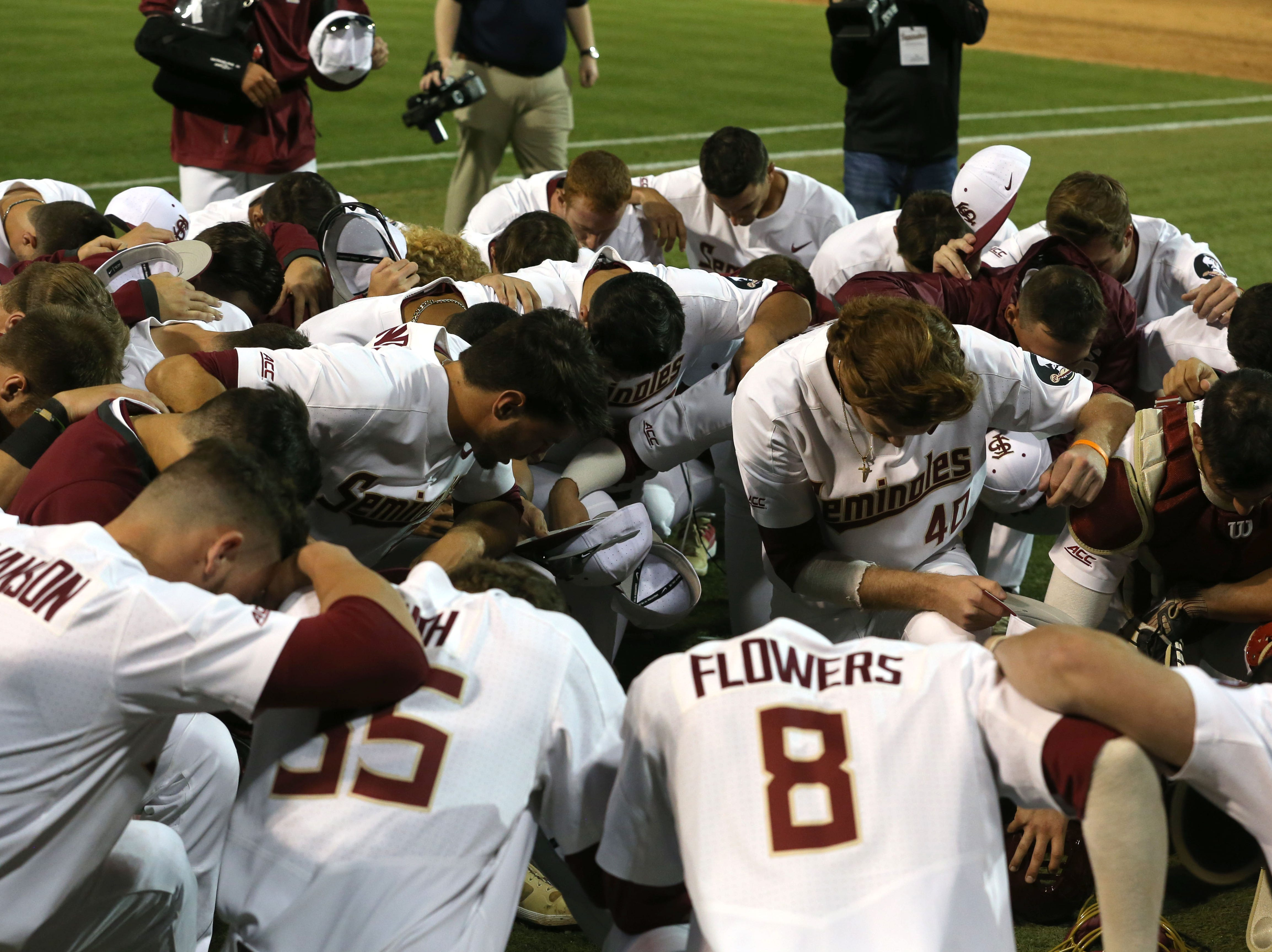 The Florida State Seminoles take a knee together after shutting out the Maine Black Bears in the 2019 season opener game, Friday Feb. 15, 2019.