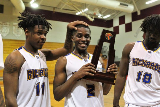 Rickards' Kelvin Dean pats Otis Young on the head while celebrating with Malik Darisaw after Rickards' boys basketball team beat Godby 58-47 during a District 2-6A championship game at Chiles on Feb. 15, 2019.