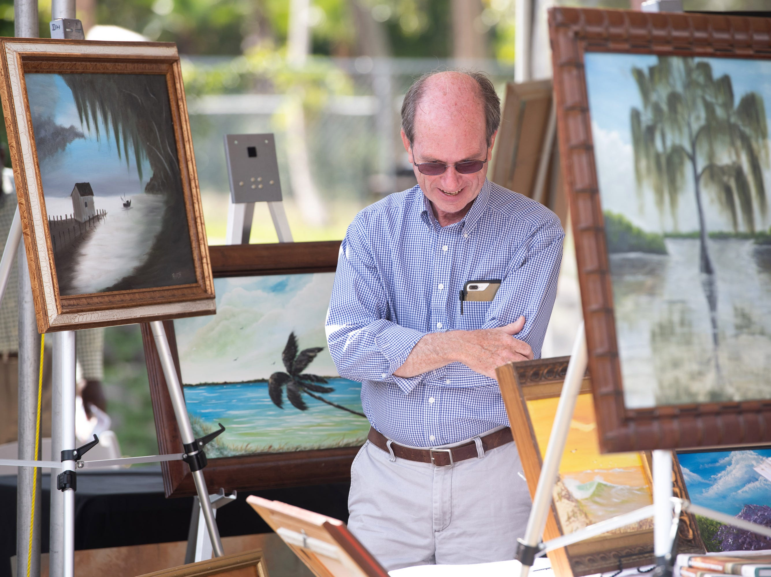 "Walter Stickley, of Port St. Lucie, looks through art at the 4th Annual Highwaymen Heritage Trail Art Show and Festival at Moore's Creek Linear Park on Saturday, Feb. 16, 2019, in Fort Pierce. ""It's a treasure to see all the Highwaymen in one place,"" Stickley said."