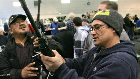 George Alvary, right, and Juan Alvary look at guns for sale in this Jan. 12, 2012, file photo from the McMann's Roadrunner Gun Show at the Ventura County Fairgrounds in Ventura.