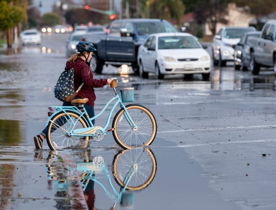 A young cyclist navigates flood waters at Court Street and Walnut Avenue after Friday's rain on Friday, February 15, 2019.