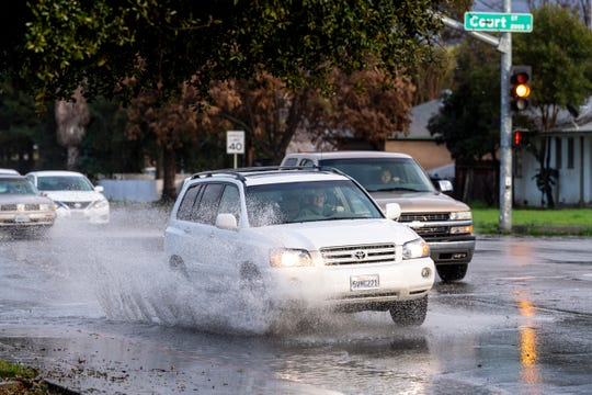 Some motorists sprayed flood waters in flooded intersections of Visalia on Friday, February 15, 2019.