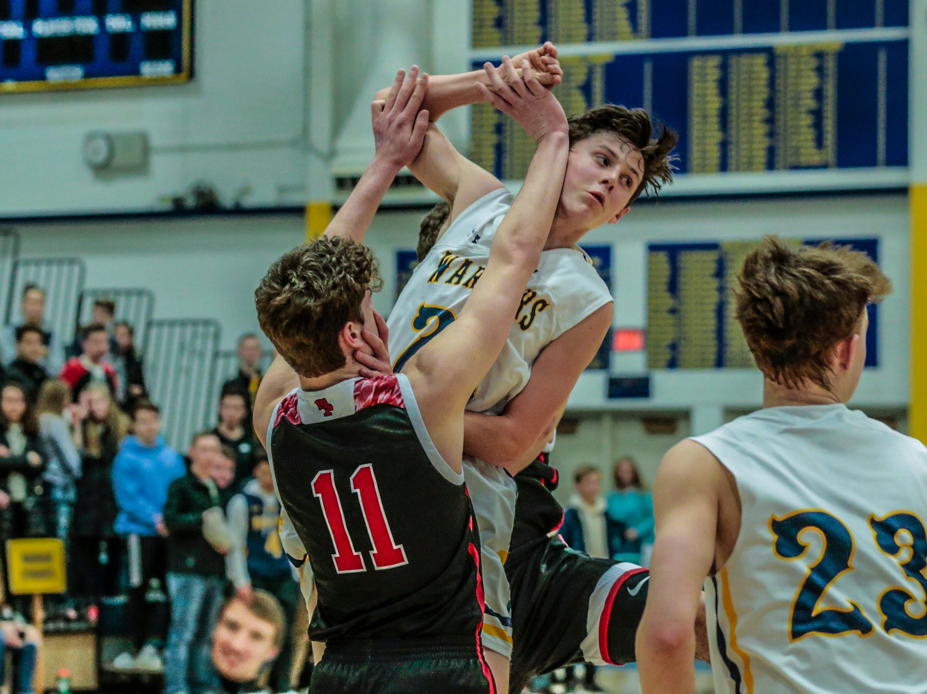 SPASH's Elliot Eron(11), left, blocks the ball off from West's Peter Fuchs(22) during Wisconsin Valley Conference boys basketball game Friday, Feb. 15, 2019, at Wausau West High School in Wausau, Wis. T'xer Zhon Kha/USA TODAY NETWORK-Wisconsin