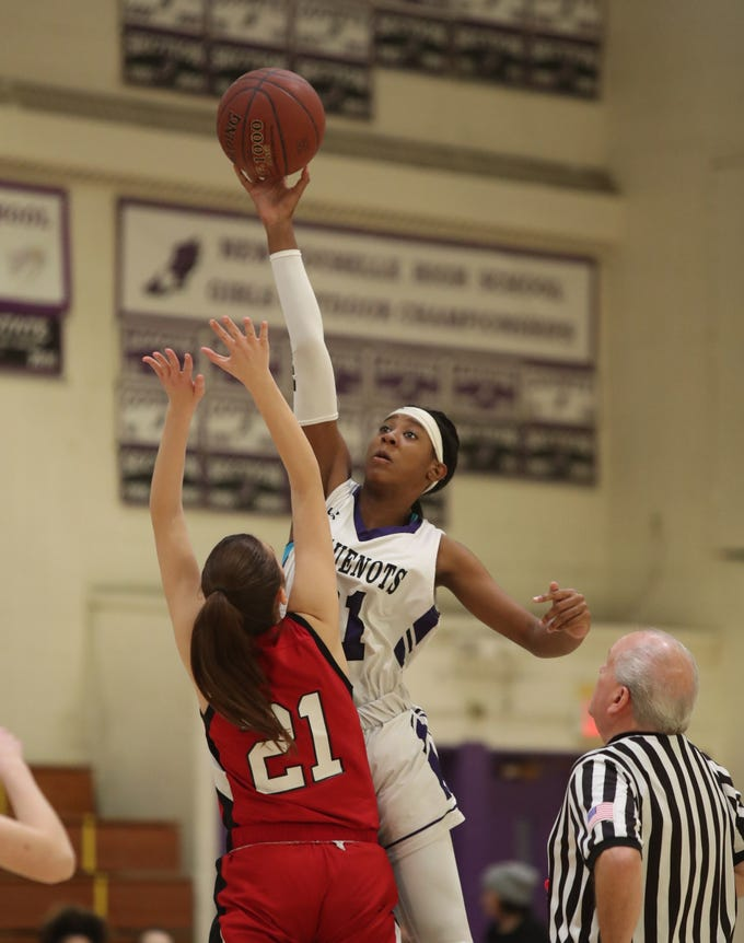 New Rochelle's Nyeira Spady (21) and Fox Lane's Sofia Zinzi (21) take the opening tip off in the class AA girls basketball outbracket game at New Rochelle High School in New Rochelle on Saturday, February 16, 2019.