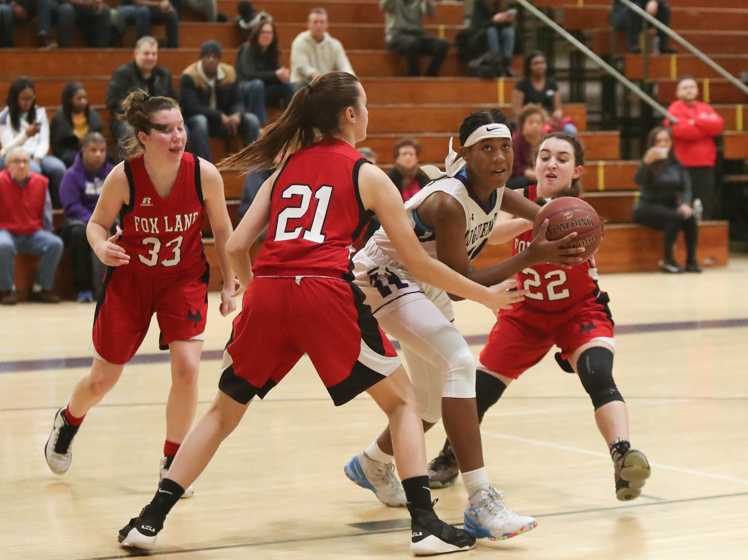 New Rochelle's Nyeira Spady (21) works hard against Fox Lane's Sofia Zinzi (21) and Nicole Picinich (22) in the class AA girls basketball outbracket game at New Rochelle High School in New Rochelle on Saturday, February 16, 2019.