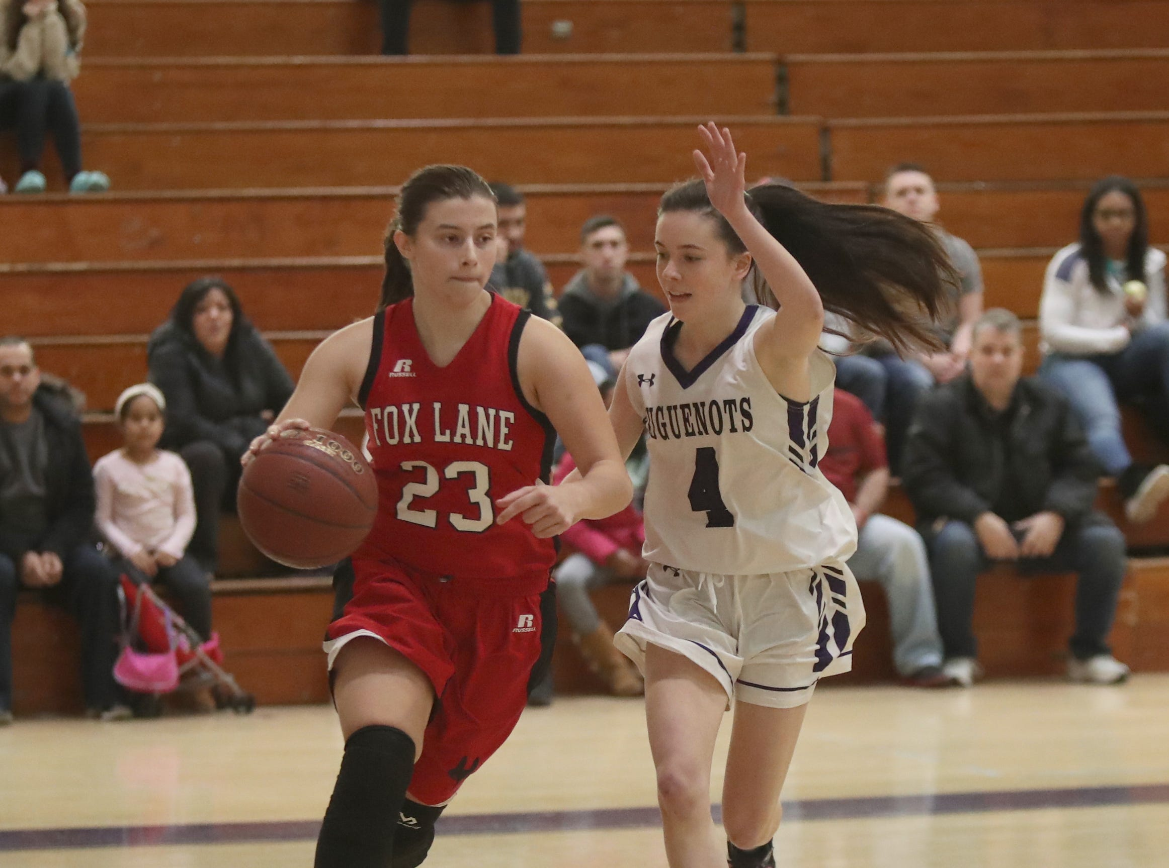 Fox Lane's Natalie Pence (23) drives the baseline as New Rochelle's Nora Fitzgerald (4) defends in the class AA girls basketball outbracket game at New Rochelle High School in New Rochelle on Saturday, February 16, 2019.