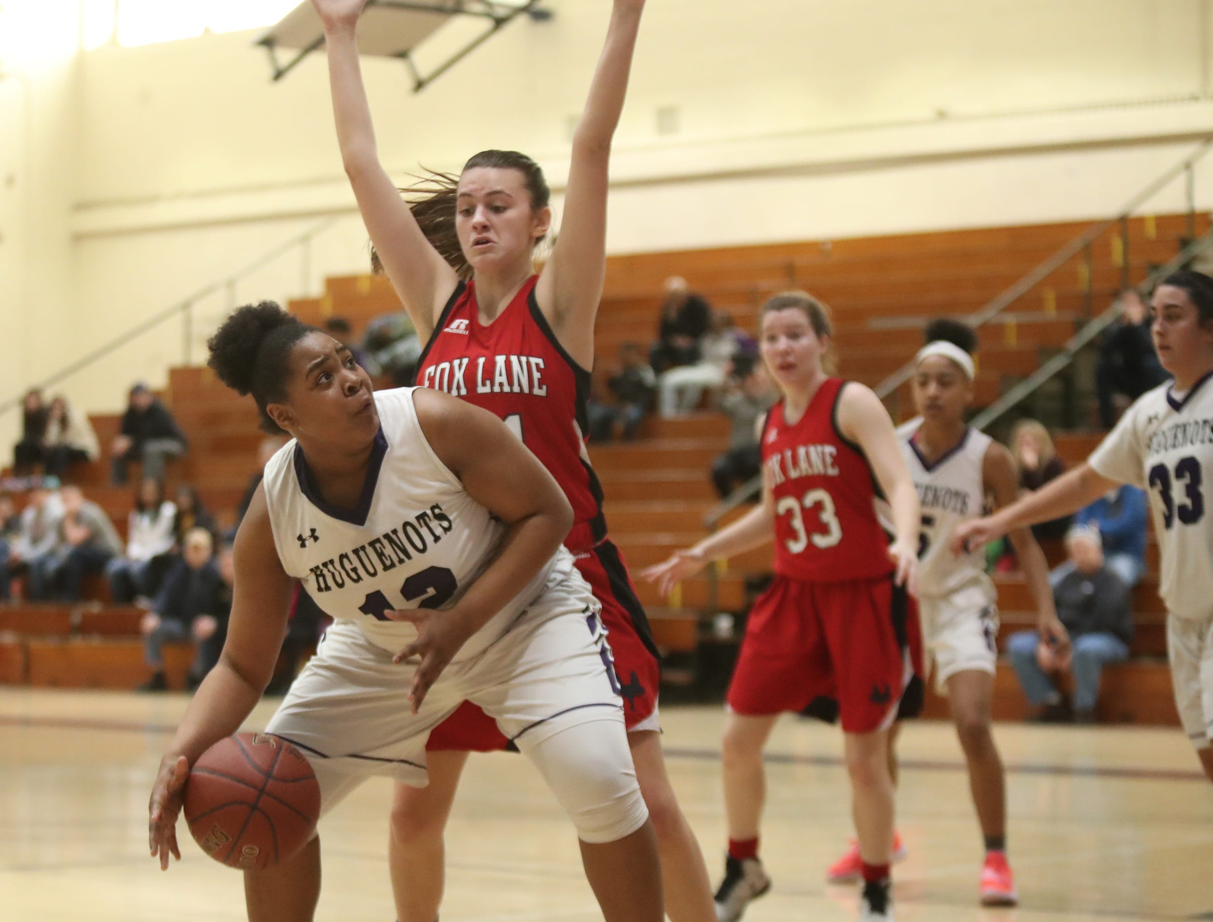 New Rochelle's Makira Bunsie (12) looks to go up strong as Fox Lane's Sofia Zinzi (21) defends in the class AA girls basketball outbracket game at New Rochelle High School in New Rochelle on Saturday, February 16, 2019.