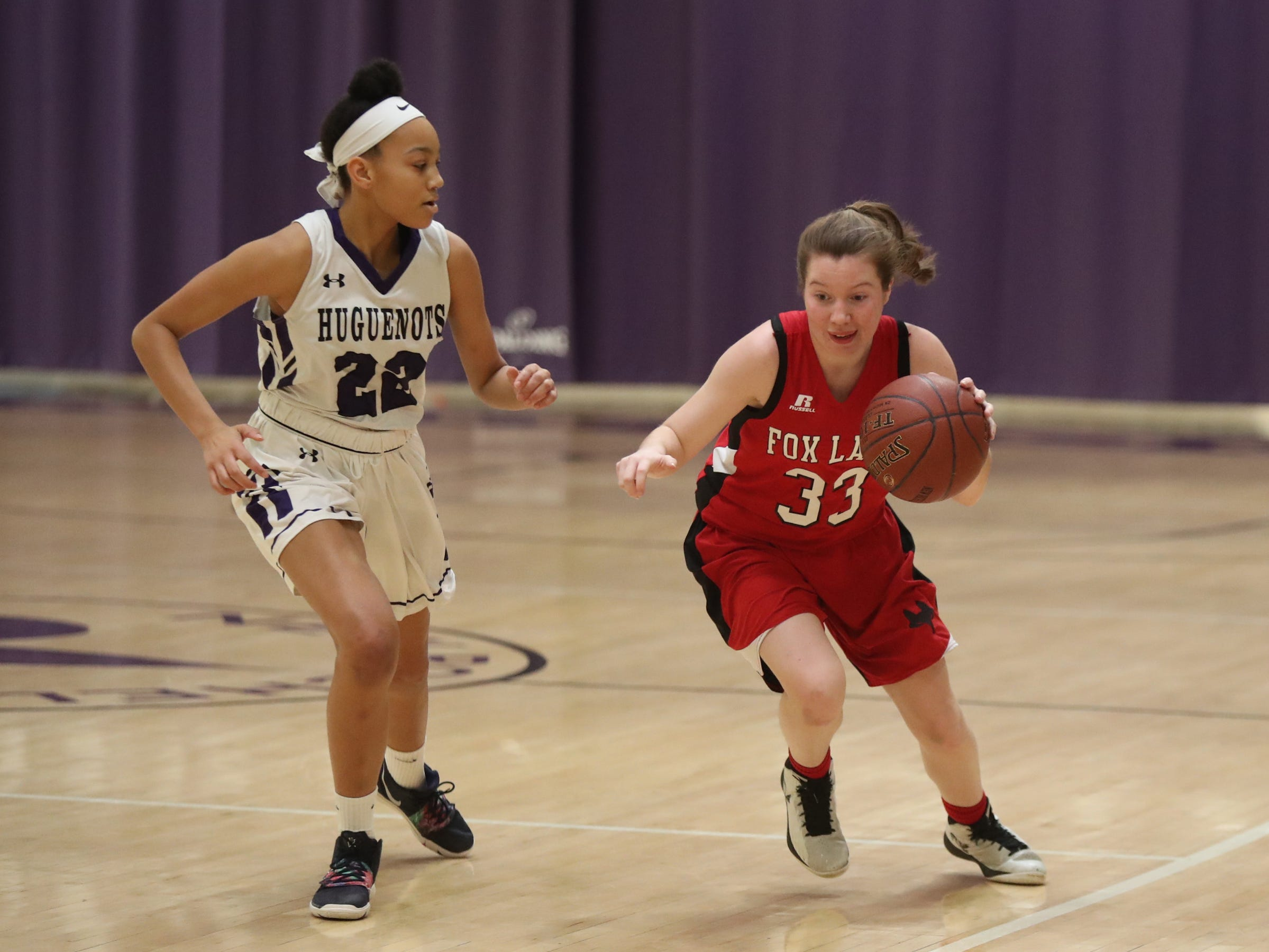 Fox Lane's Suzy Paul (33) works the ball around New Rochelle's Kamara St. Paul (22) in the class AA girls basketball outbracket game at New Rochelle High School in New Rochelle on Saturday, February 16, 2019.