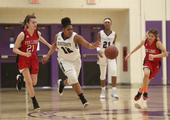 New Rochelle's Makira Bunsie (12) charges for a loose ball as Fox Lane's Sofia Zinzi (21) chases in the class AA girls basketball outbracket game at New Rochelle High School in New Rochelle on Saturday, February 16, 2019.