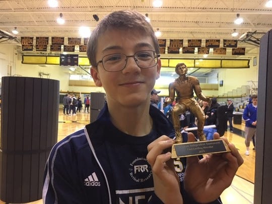 Sanford 132-pound Justin Griffith shows off his Outstanding Wrestler award.