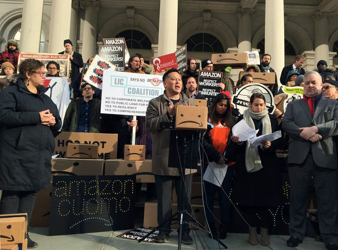 FILE - In this Dec. 12, 2018 file photo, New York State Assemblyman Ron Kim, center, speaks at a rally opposing New York's deal with Amazon on the steps of New York's City Hall. Those opposed to the new Amazon campus had a long list of grievances: the deal was done secretively; Amazon didn't need nearly $3 billion in tax incentives; and rising rents could push people out of the neighborhood. (AP Photo/Karen Matthews, File)
