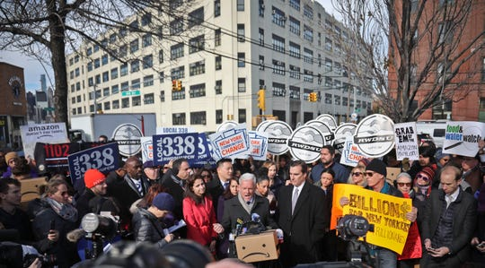 FILE - In this Nov. 14, 2018 file photo, New York City Councillor Jimmy Van Bramer, center, speaks during a coalition rally and press conference of elected officials, community organizations and unions opposing Amazon headquarters getting subsidies to locate in the New York neighborhood of Long Island City, Queens. Some people asked why Amazon, one of the world's most valuable companies, needed nearly $3 billion in tax incentives to come to New York. (AP Photo/Bebeto Matthews, File)