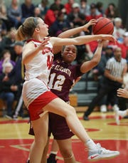 Conrad's Stefanie Kulesza (left) reaches for a rebound against St. Elizabeth's Arianna	Henry in Conrad's 73-59 win against St. Elizabeth Friday.