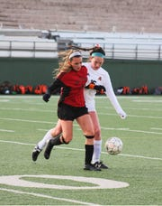 Old High's Alyssa Salinas shields the ball from Aledo's Hunter Jones at Memorial Stadium Friday, February 15, 2019. Salinas scored the only goal for the Coyotes.
