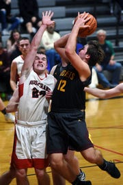 Zane Mirgon, of Berne Union, goes up for a shot in the lane over Rosecrans' Weston Nern in Zanesville. The Bishops won the game, 59-46, despite Mirgon's game-high 22 points.