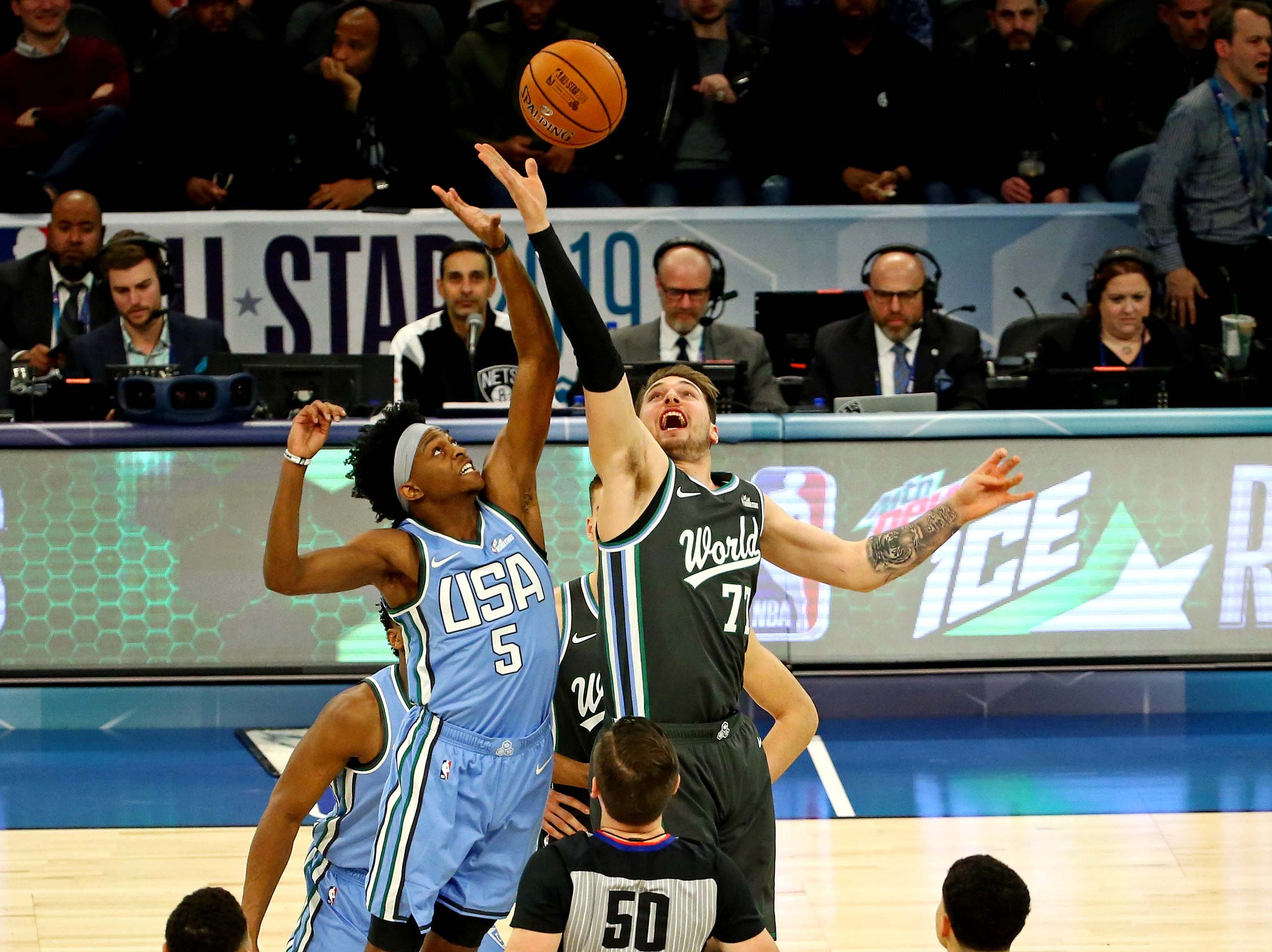World Team guard Luka Doncic of the Dallas Mavericks and U.S. Team guard De'Aaron Fox of the Sacramento Kings go for the opening tip during the All-Star Rising Stars game.