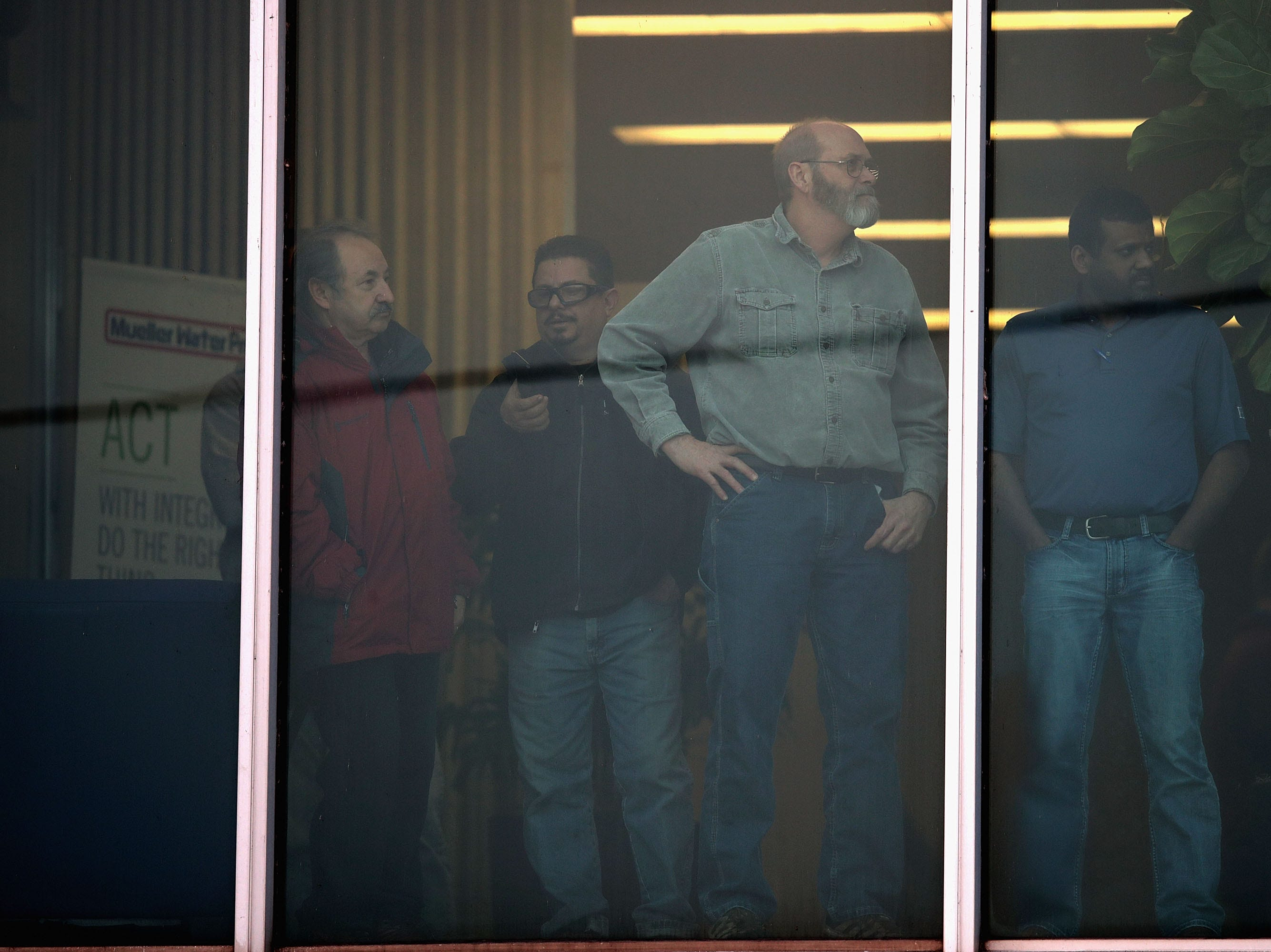 Workers look out an office window following a shooting at the Henry Pratt Company on February 15, 2019 in Aurora, Illinois.