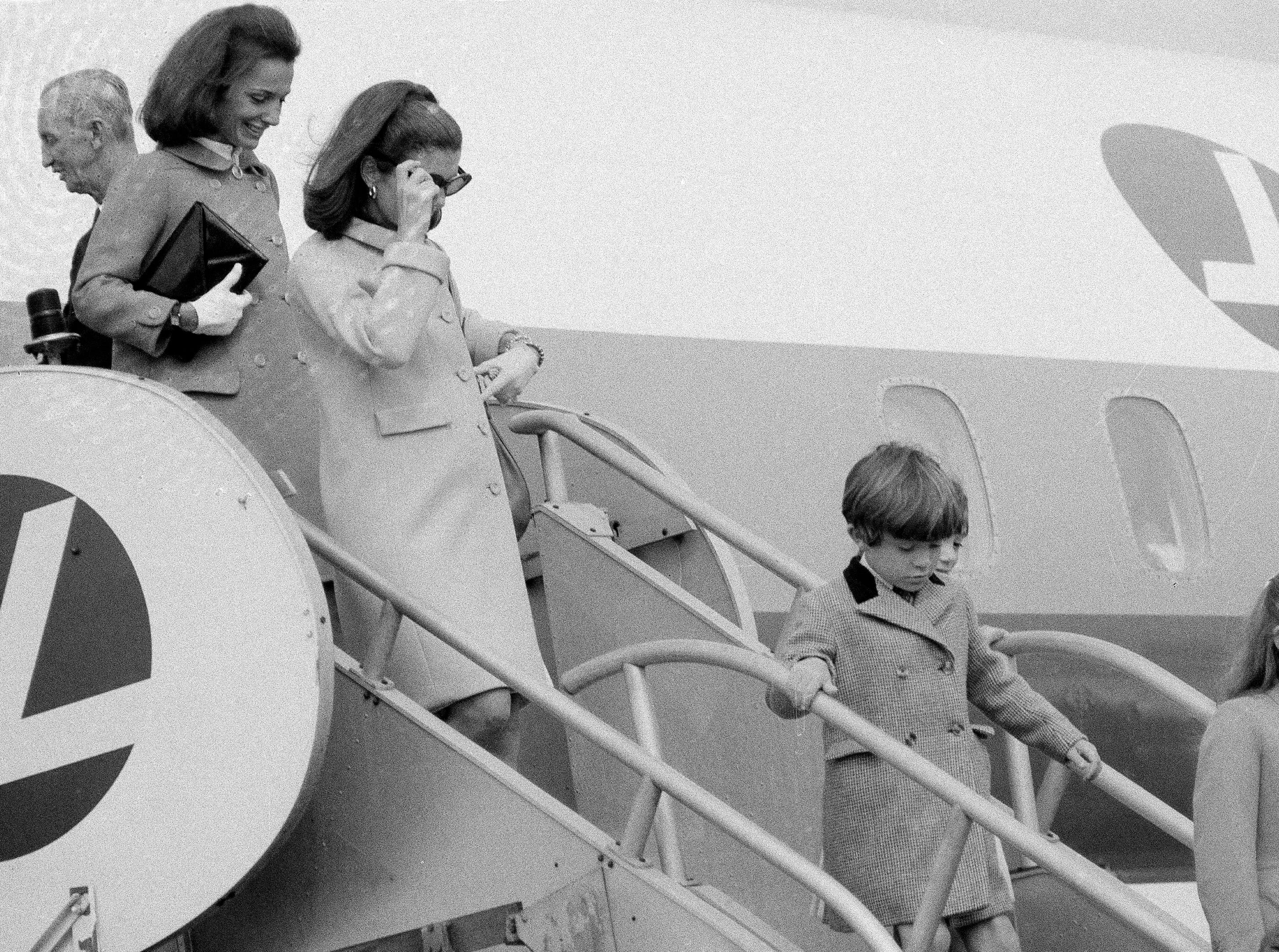 Jacqueline Kennedy, left, leaves plane on arrival at Kennedy Airport in New York, after a vacation in Acapulco, Mexico, March 28, 1967. Mrs. Kennedy's children, John and Caroline are at right. Behind them are the two children of Mrs. Kennedy's sister, Princess Lee Radziwill, Anthony and Anna Christine.