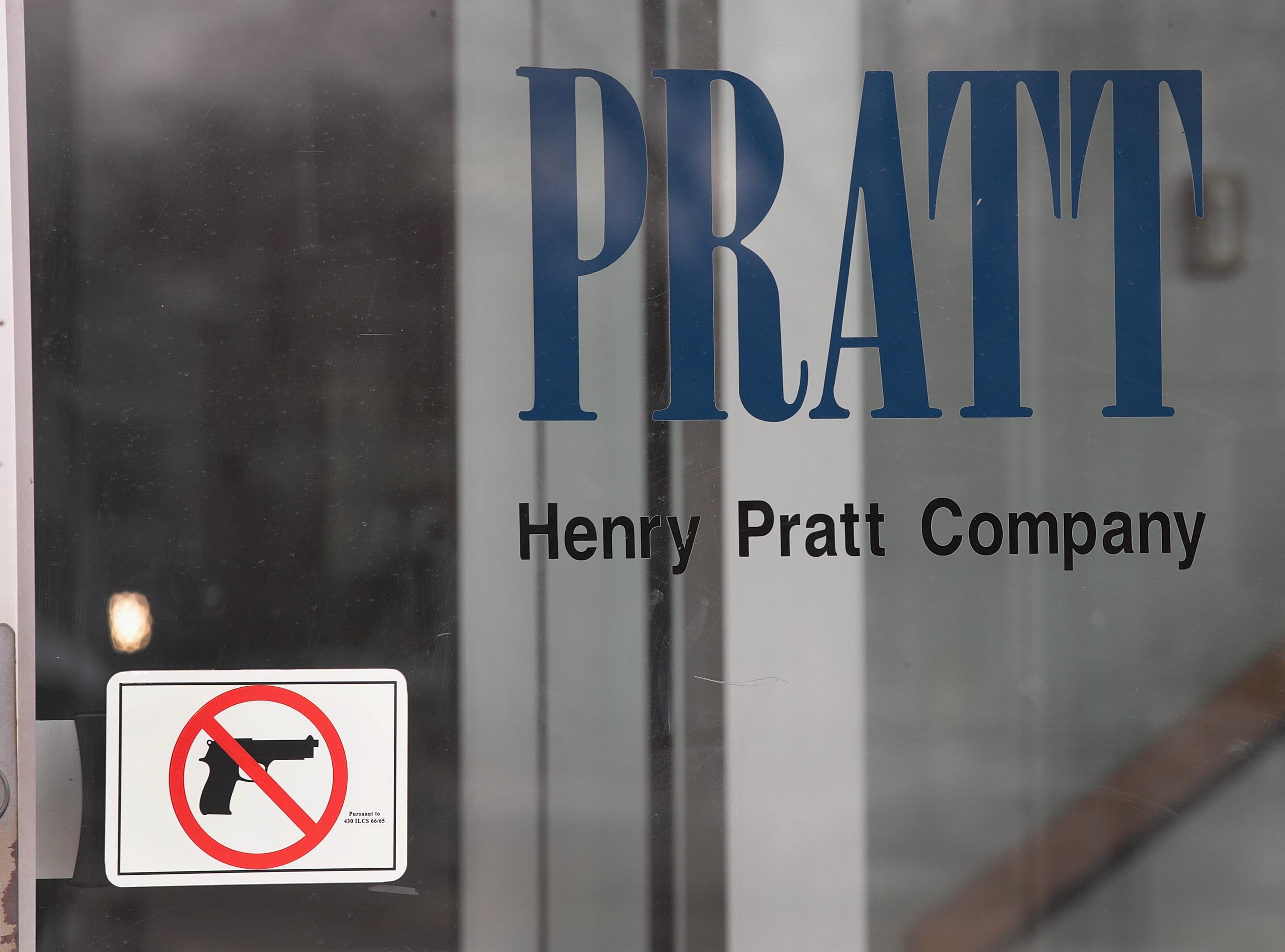 A sign on the front door of the Henry Pratt Company office shows that guns are not allowed in the building on Feb. 16, 2019 in Aurora, Ill. Yesterday five people were killed and 5 police officers were wounded by a former employee armed with a handgun in the company's manufacturing plant. The gunman, who was killed by police, has been identified as Gary Martin.