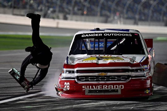 Bryan Dauzat (28) hits his jackman and sends him flying during a pit stop in the NASCAR Truck Series season opener