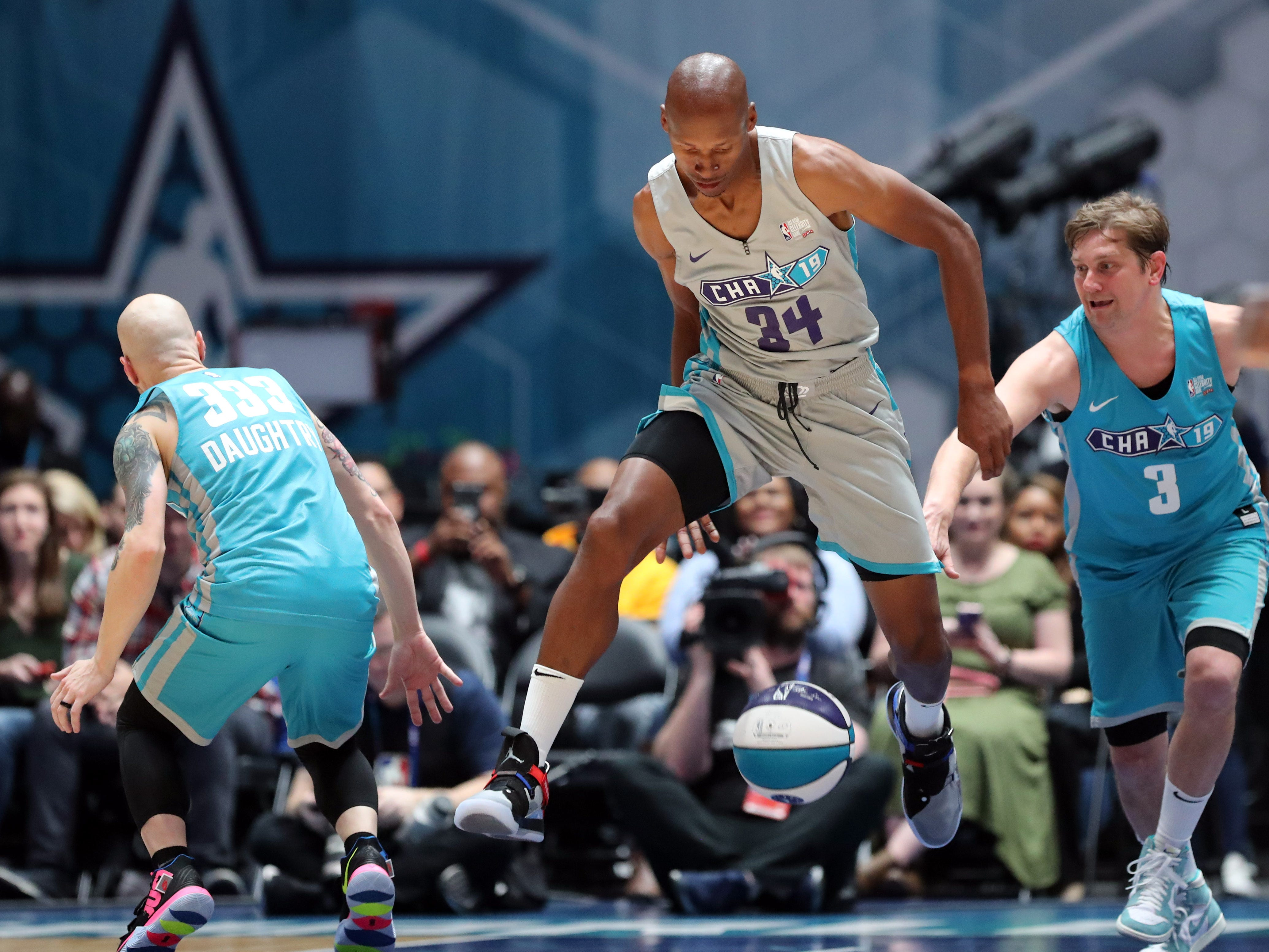 Ray Allen brings the ball up the court while defended by Bo Rinehart (3) and Chris Daughtry during the Celebrity Game.